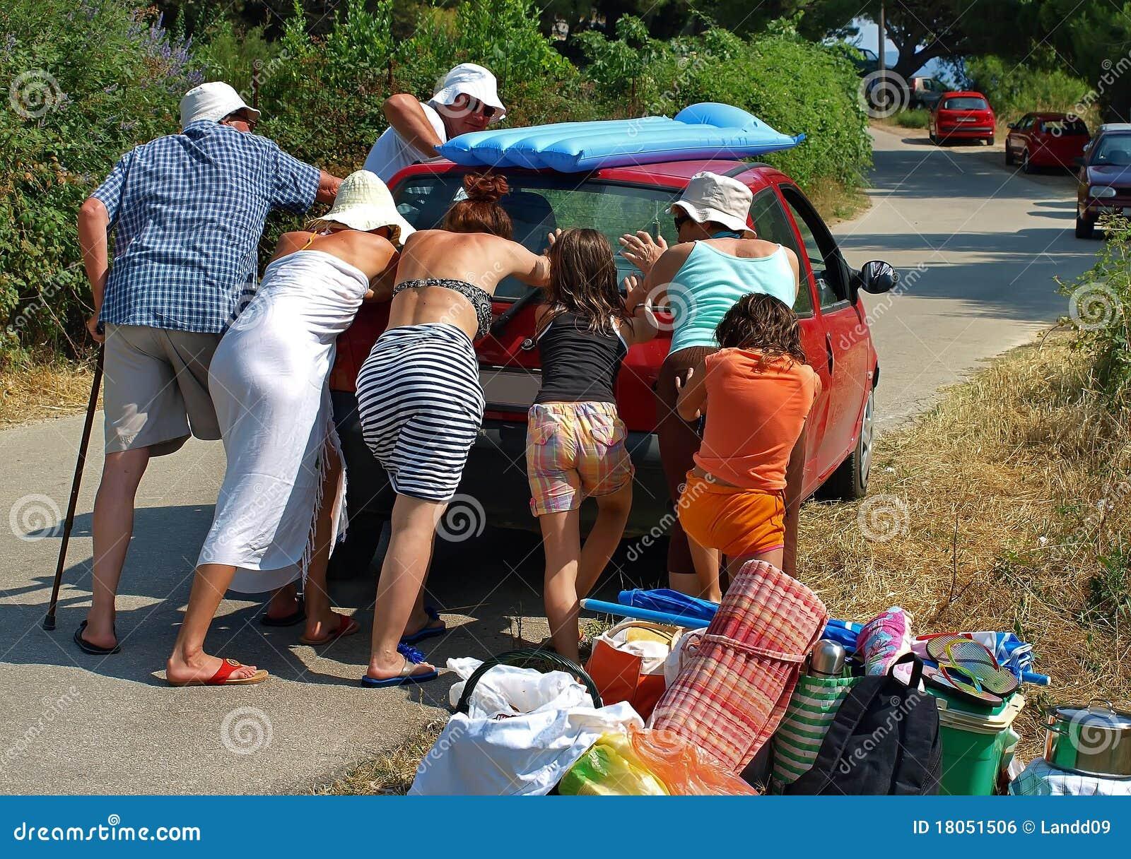 People pushing a car