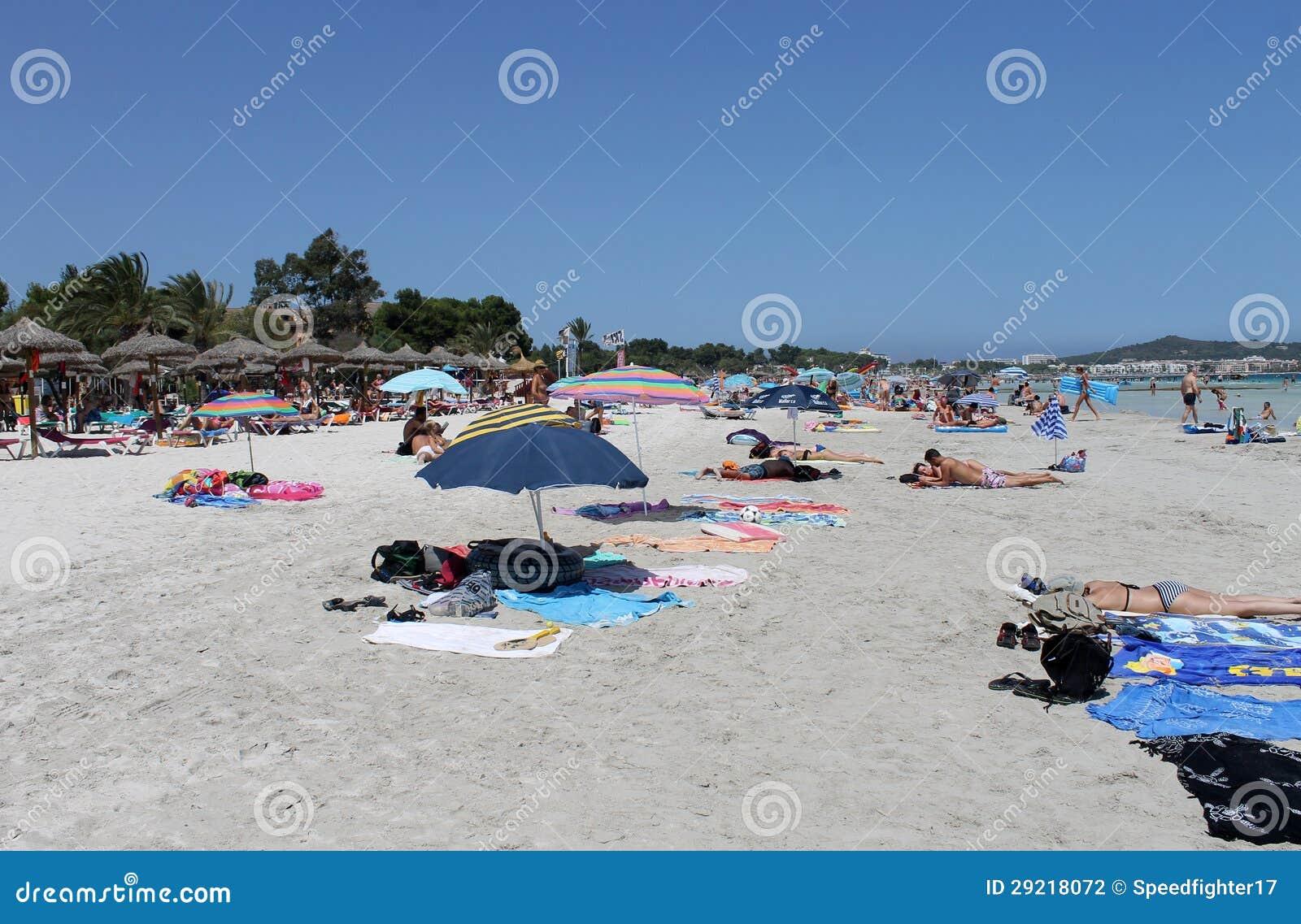 People Relaxing On Beach In Majorca