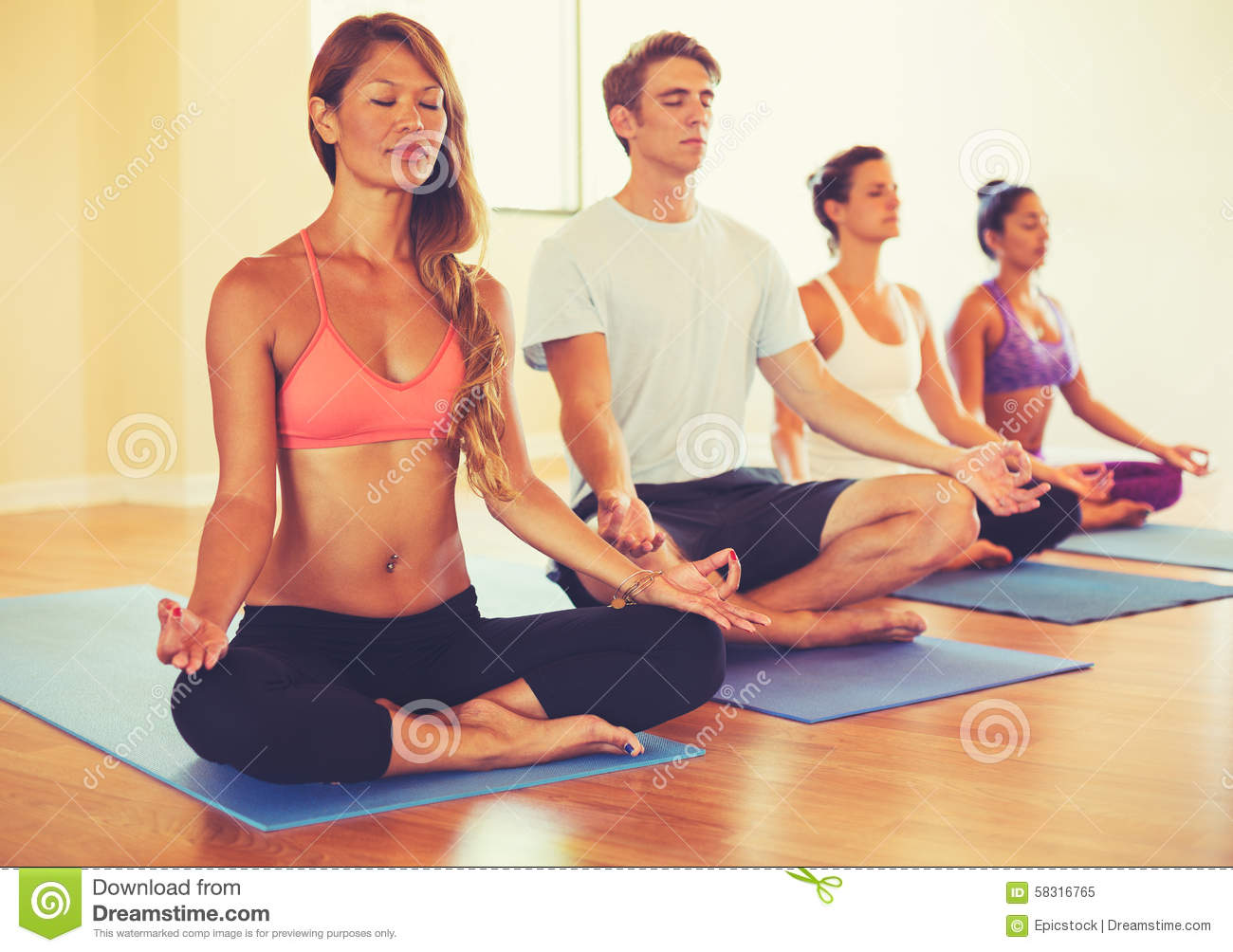 People Relaxing And Meditating In Yoga Class Stock Photo