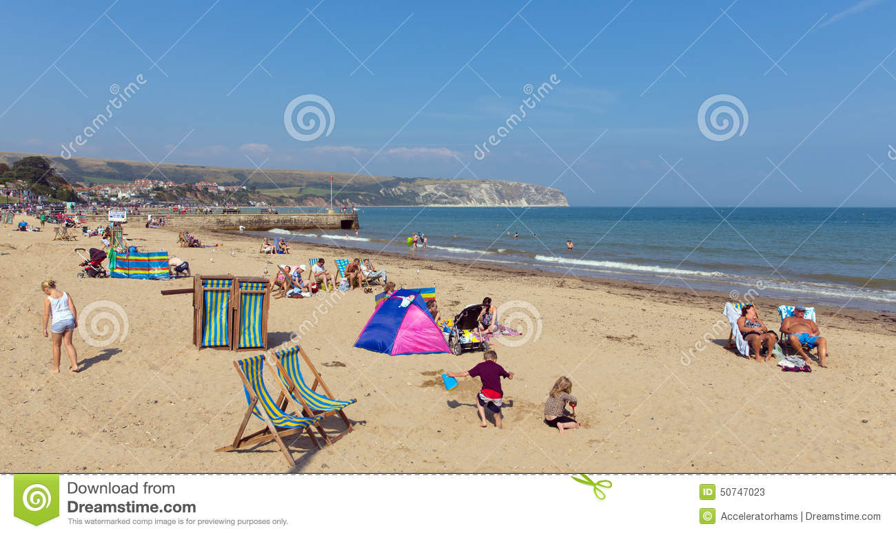 People Relaxing In Summer Sunshine Swanage Beach Dorset England UK With Waves On The Shore