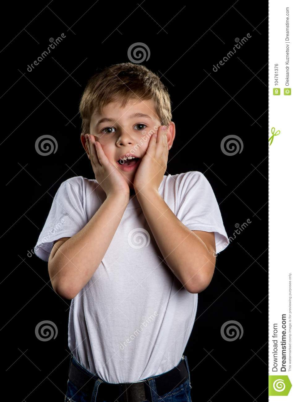 People`s emotions. Surprised boy portrait with palms holding on the cheeks on the black background