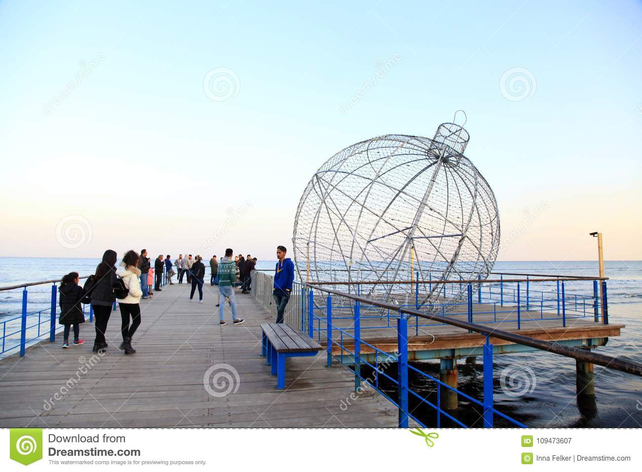 People on sea waterfront with giant christmas ball decoration in