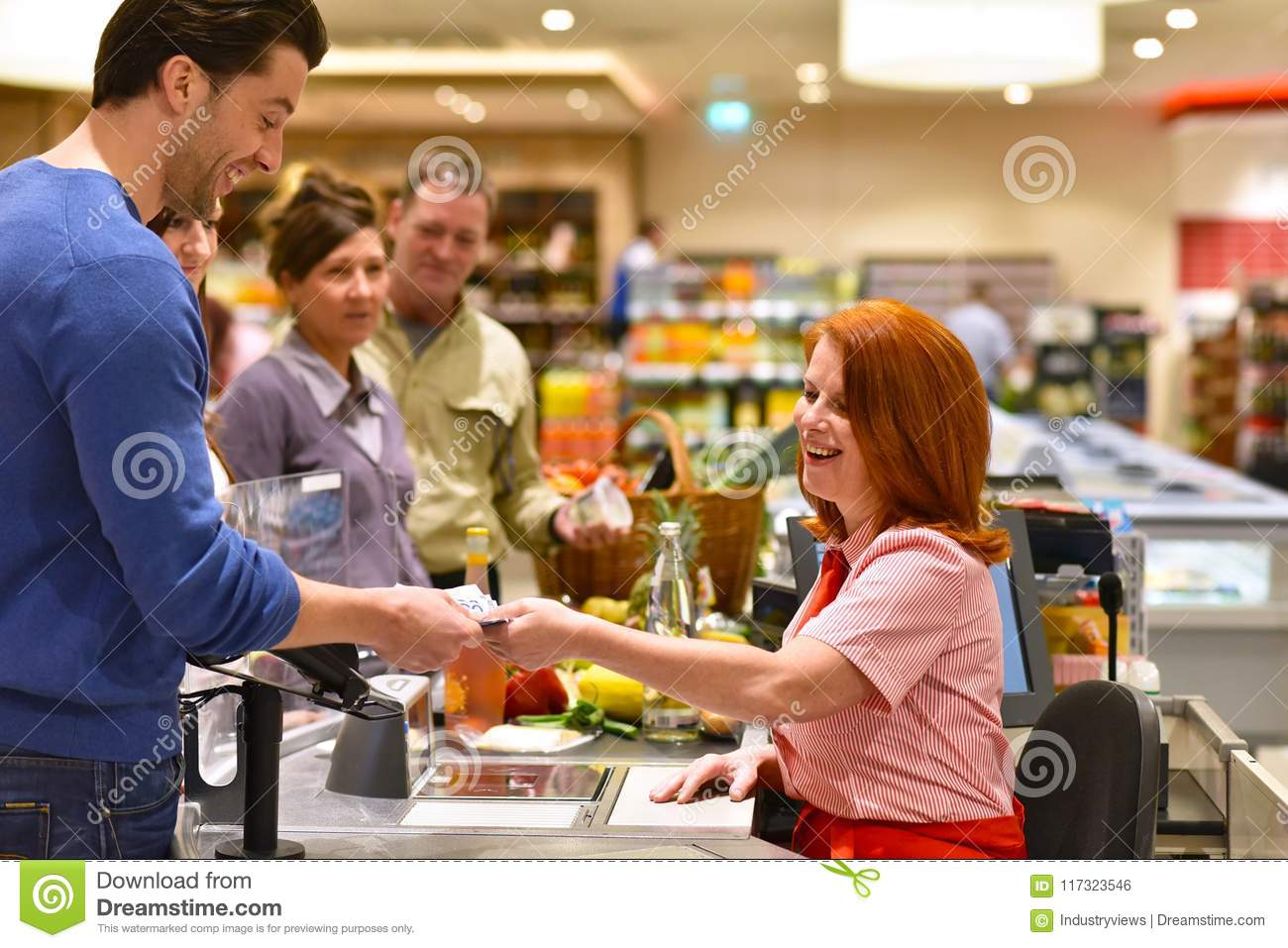 People shopping for food in the supermarket - checkout paying