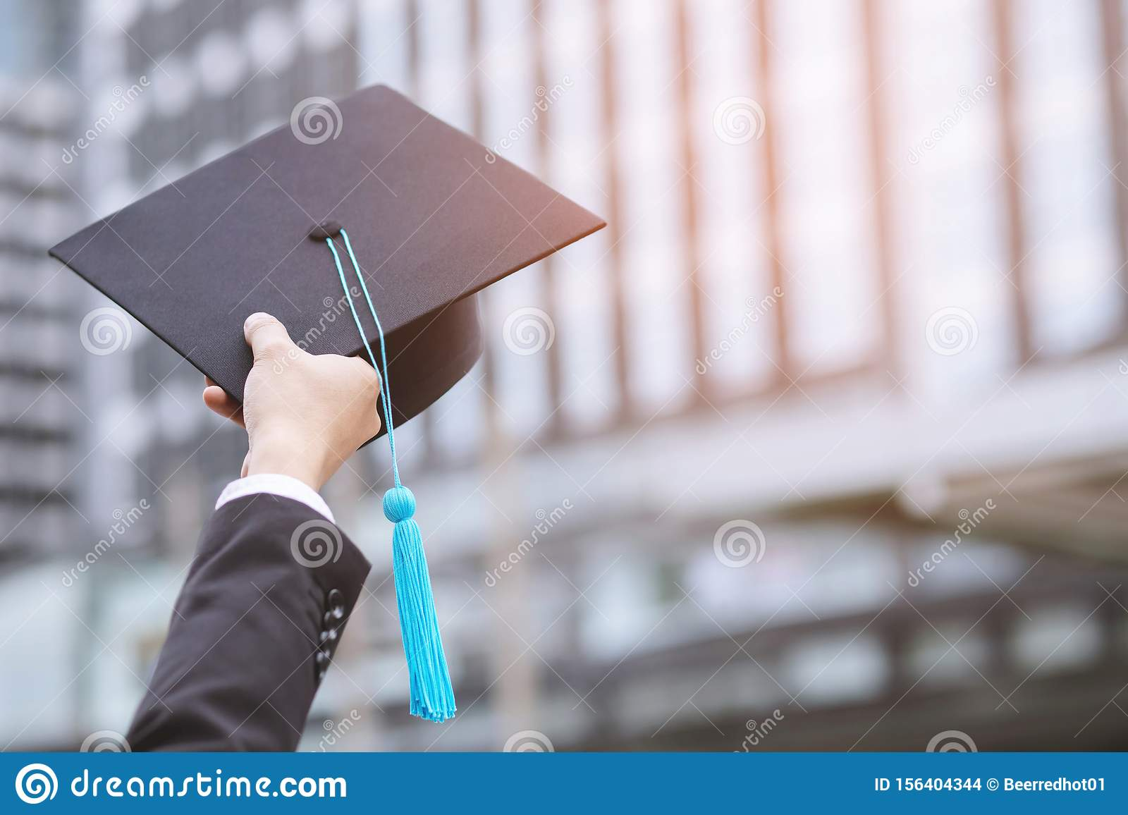 People show hand hold show hat Blue tassels in background School building. Shot of graduation cap during Commencement University D