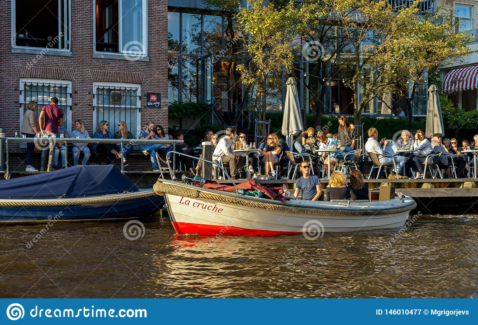 People sitting in Cafe restaurant on the canal in Amsterdam with parked small city tour boat, the Netherlands, October 13, 2017