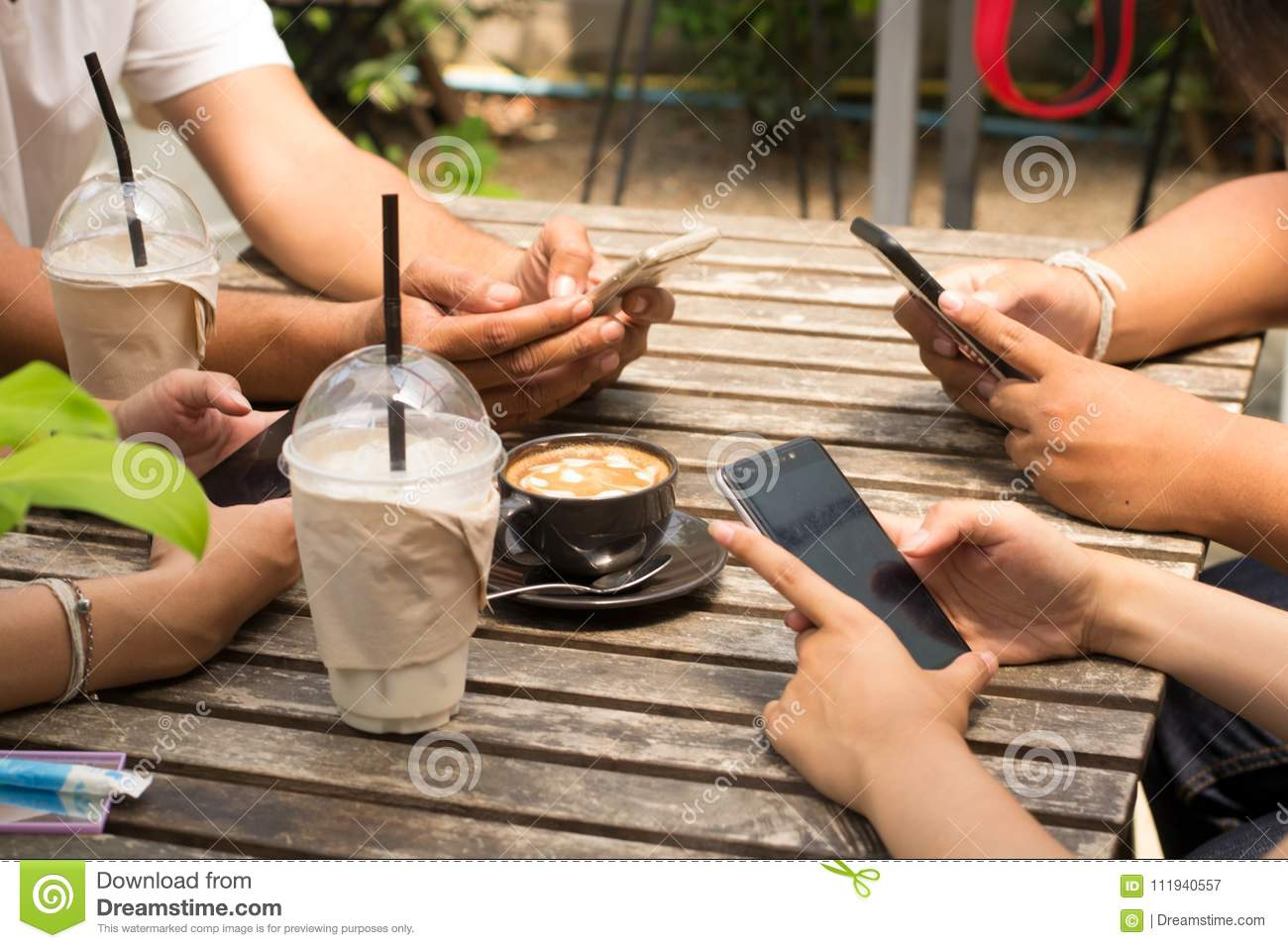People are sitting on the phone and drinking coffee on a wooden table in a restaurant.