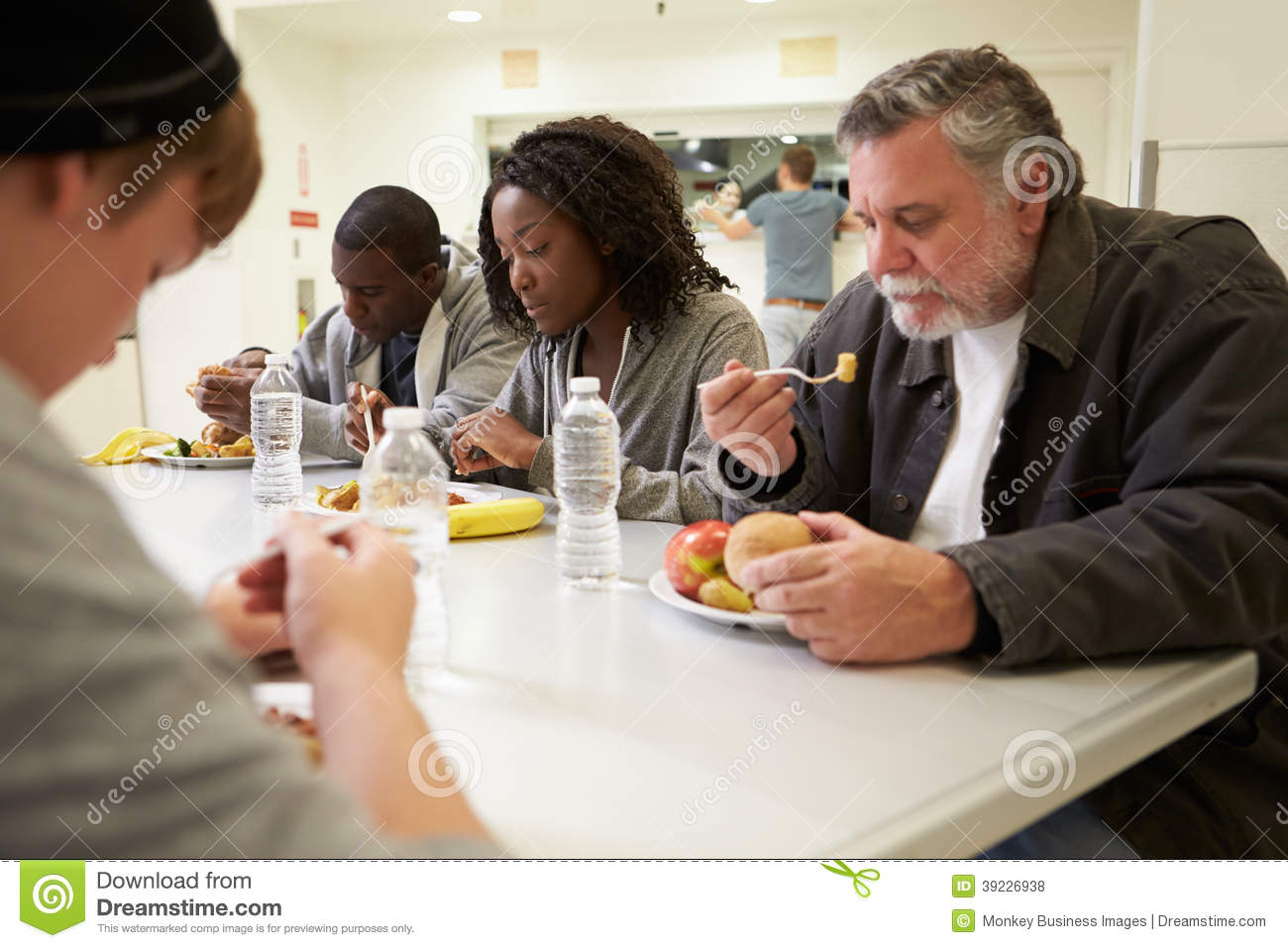 People sitting at table eating food in homeless shelter for Eating table