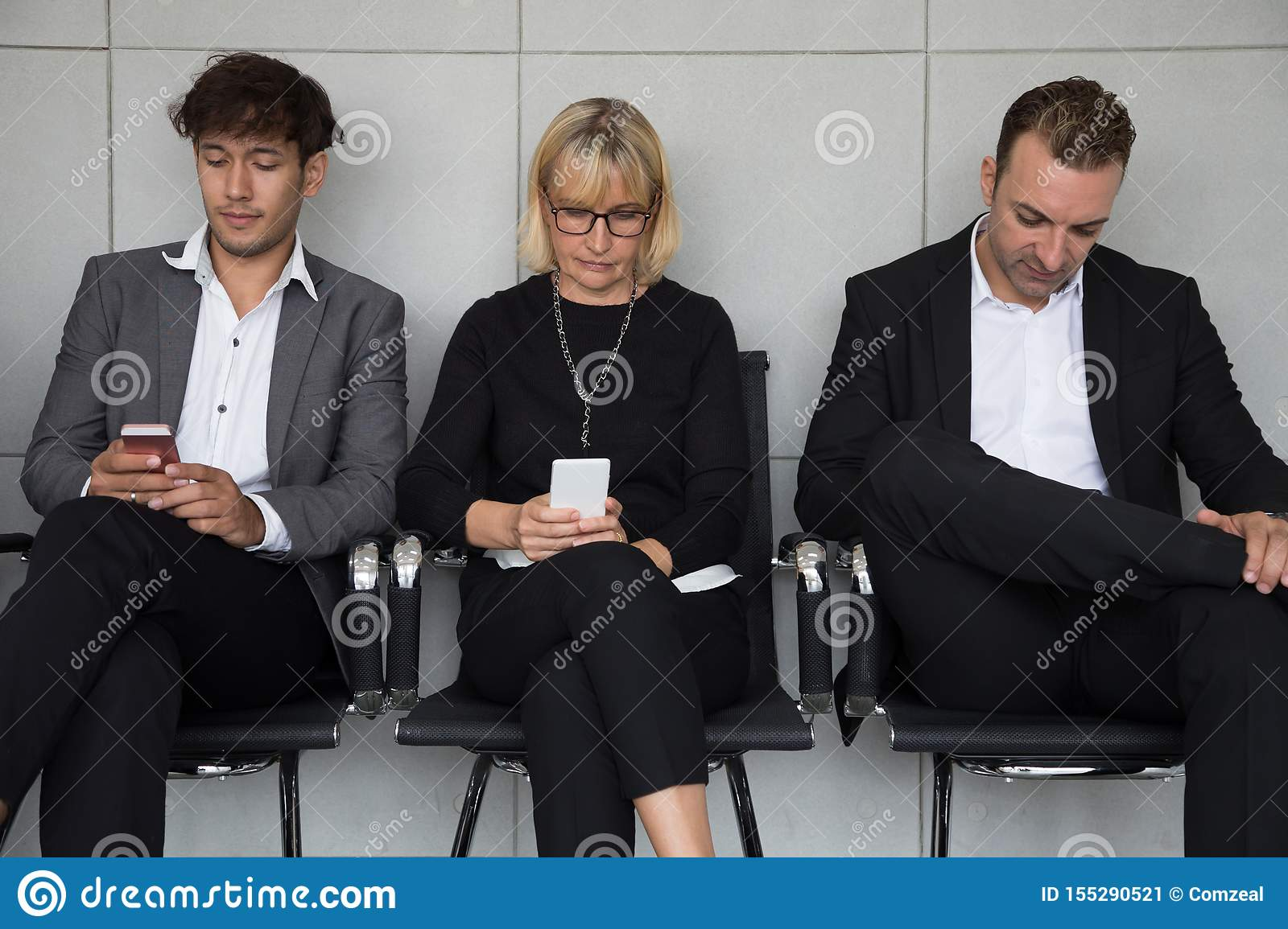 People sitting waiting for a job interview and using social media application on mobile phone.