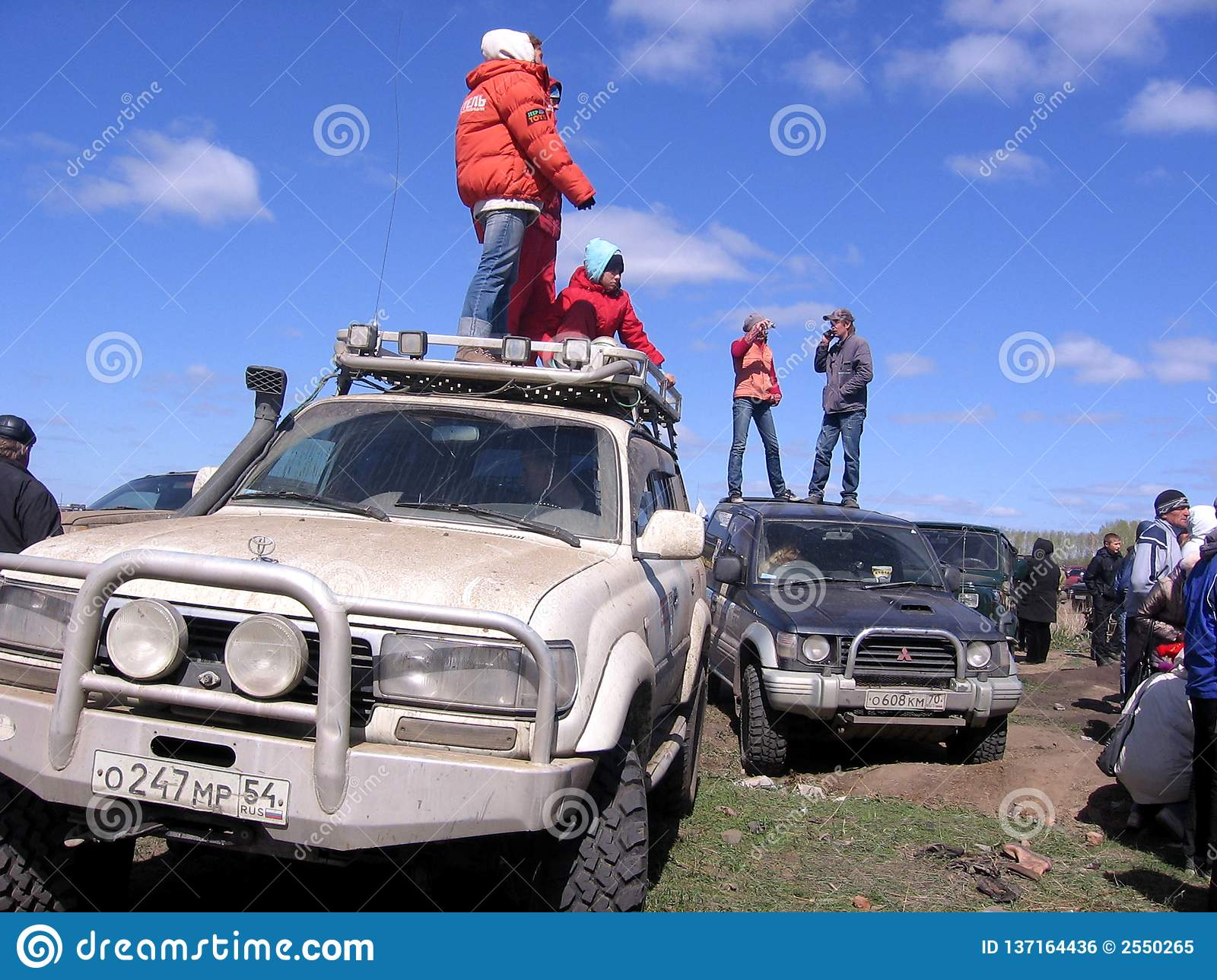 People stand on the roof of the jeeps racing SUVs crowd of spectators watching a stuck car being pushed out of the mud