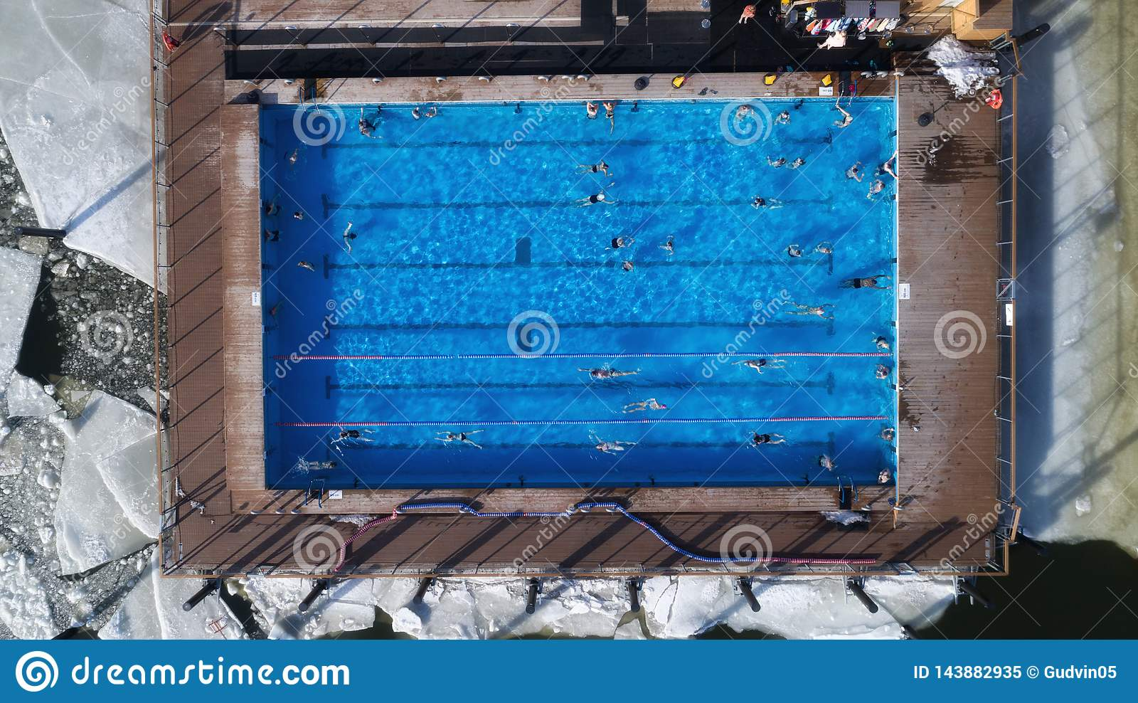 People swimming in the pool at winter top view angle