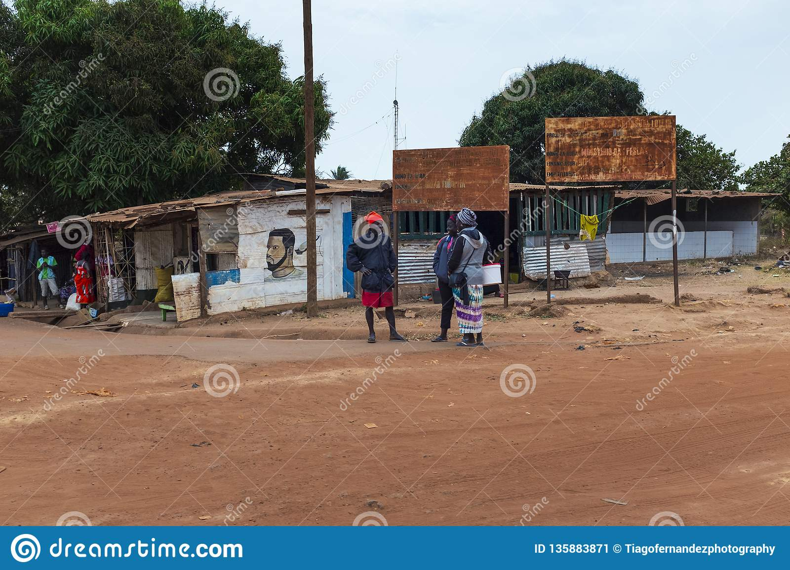People talking near a barbershop in a slum at the city of Bissau, in Guinea-Bissau