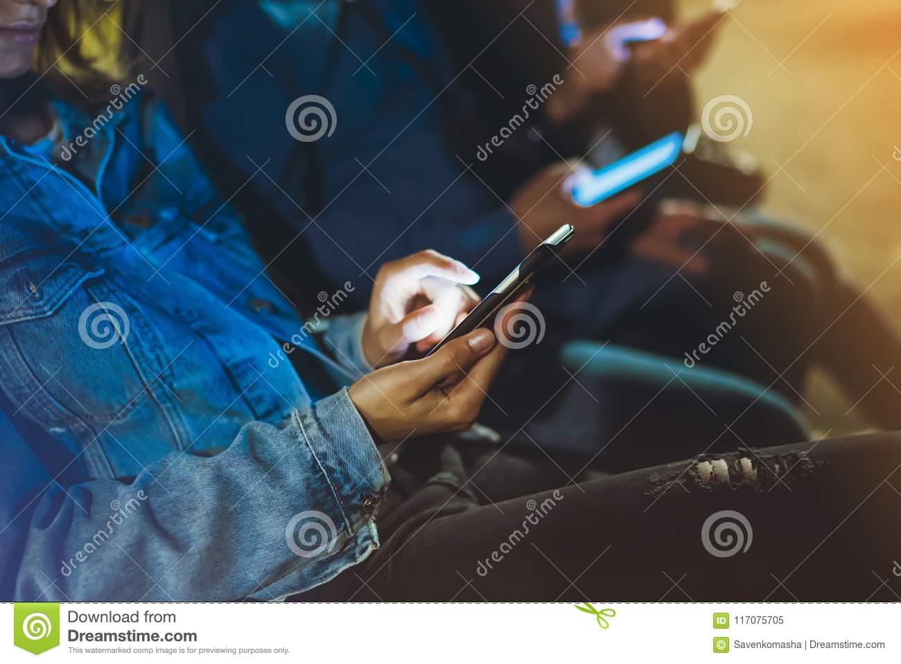 People together pointing finger on screen smartphone on background bokeh light in night atmospheric city, group adult hipsters fri