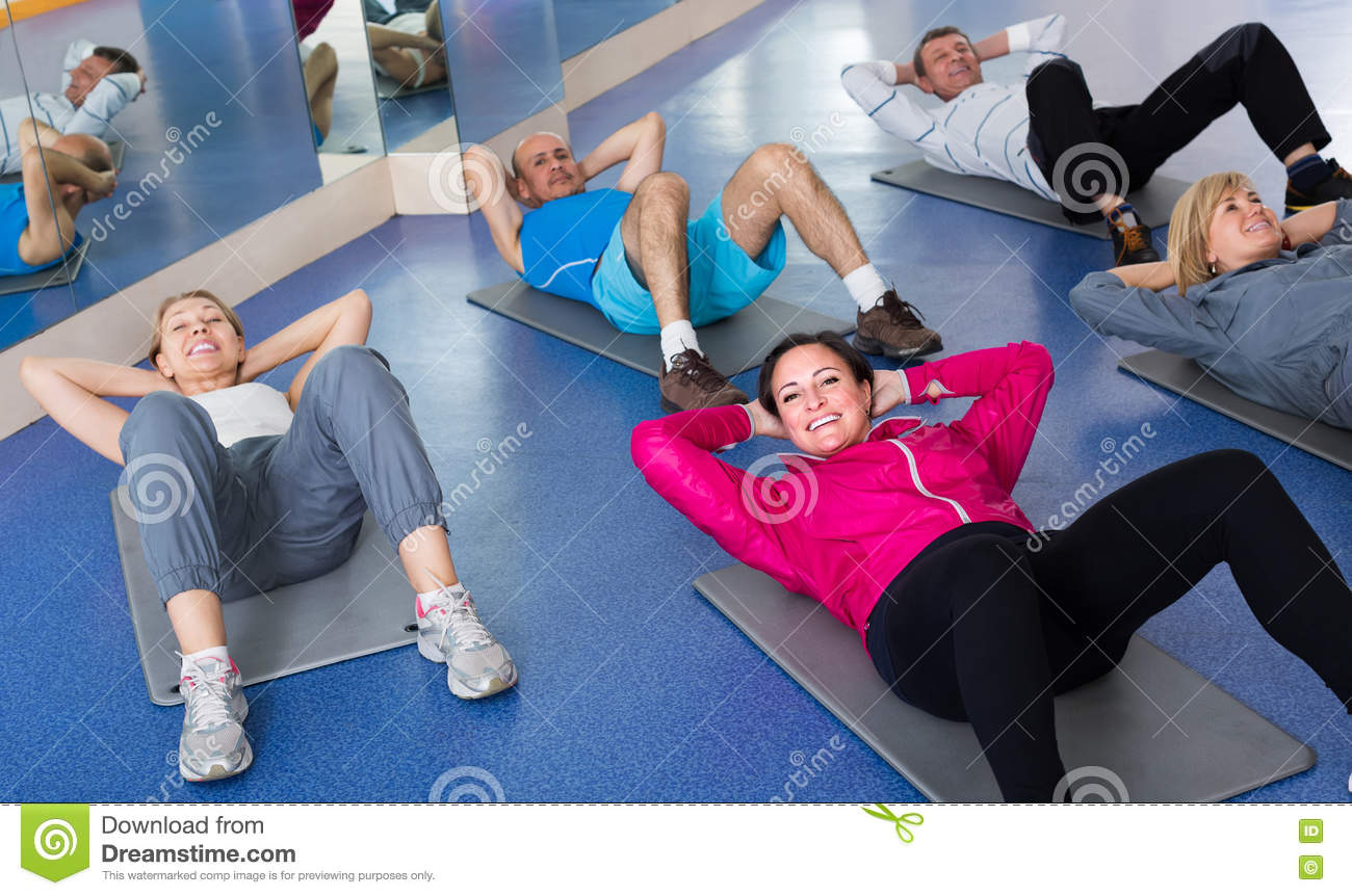 People training in a gym on sport mats