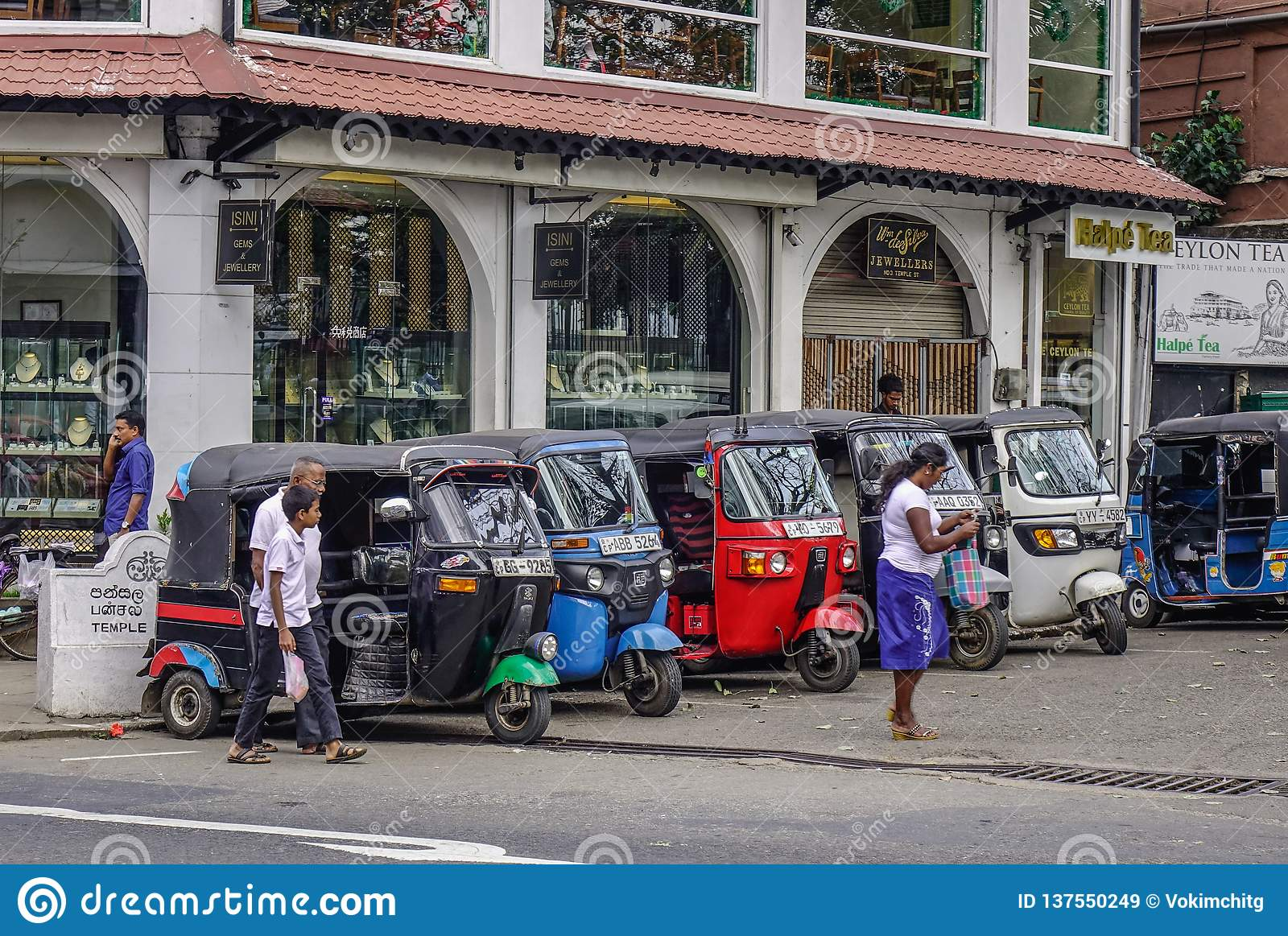 People and tuk tuk taxis on street