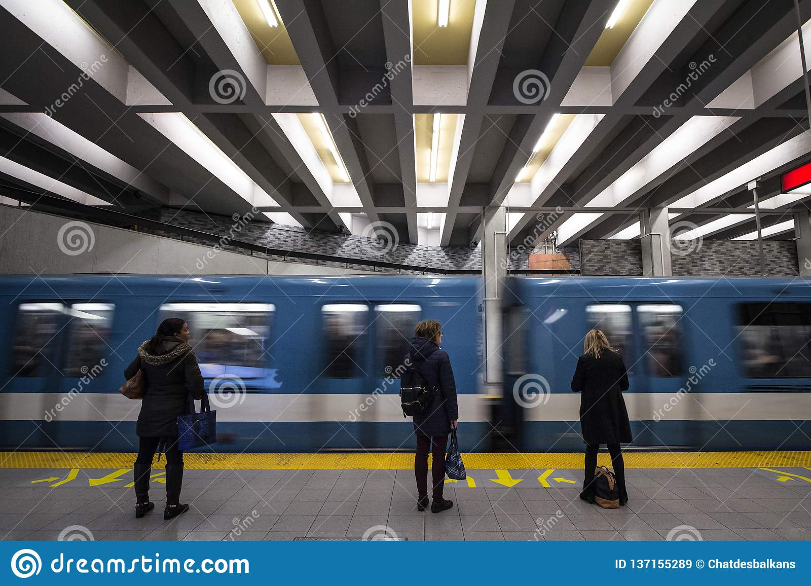 People waiting for a subway in Berri-UQAM station platform, green line, while a metro train is coming, with a speed blur