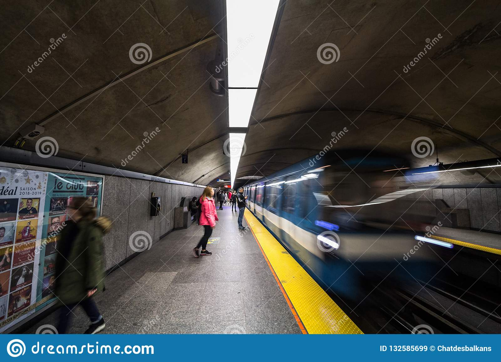 People waiting for a subway in Cote des Neiges station platform, blue line, while a metro train is coming, with a speed blur