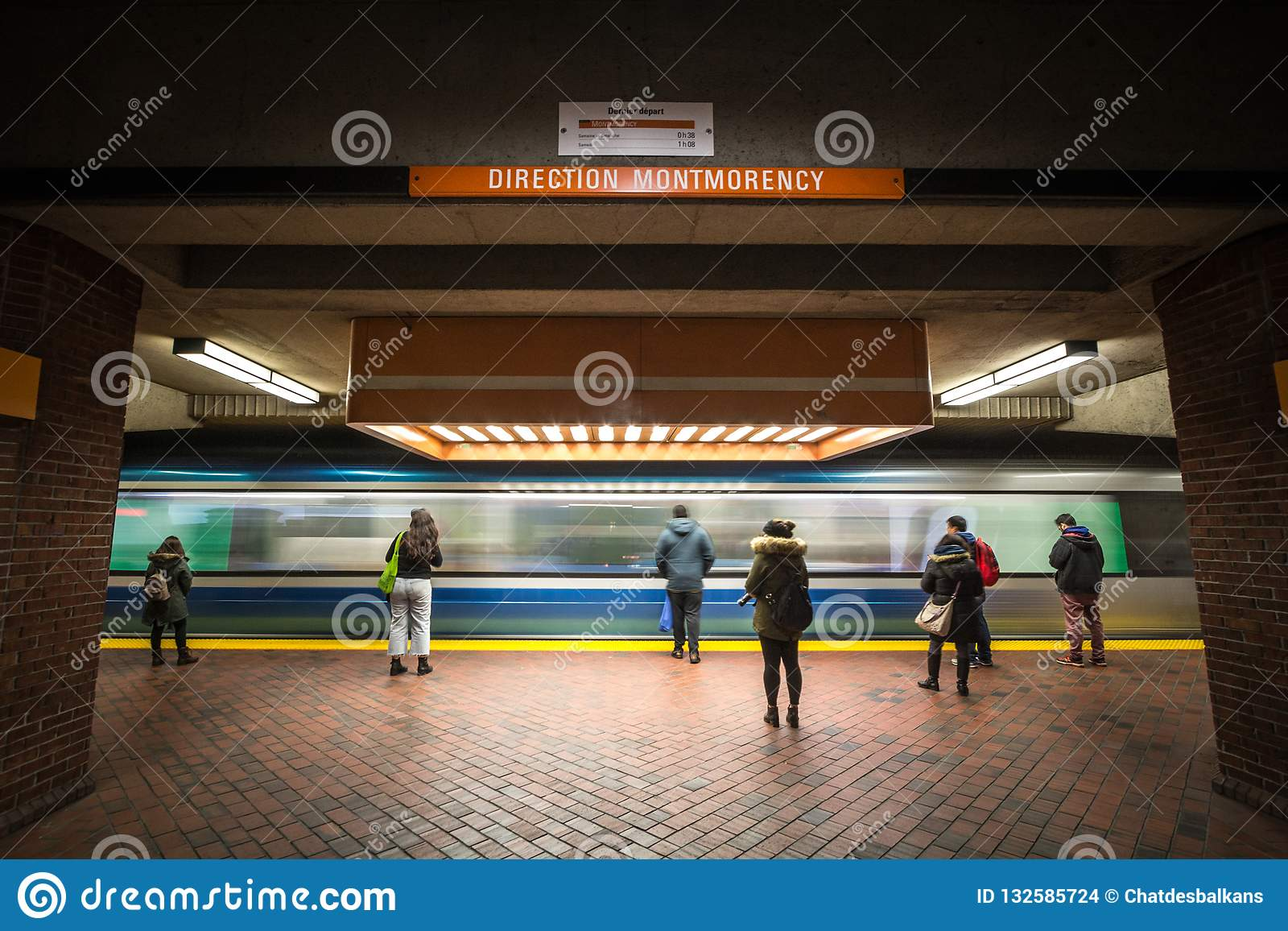 People waiting for a subway in Snowdon station platform, orange line, while a metro train is coming, with a speed blur