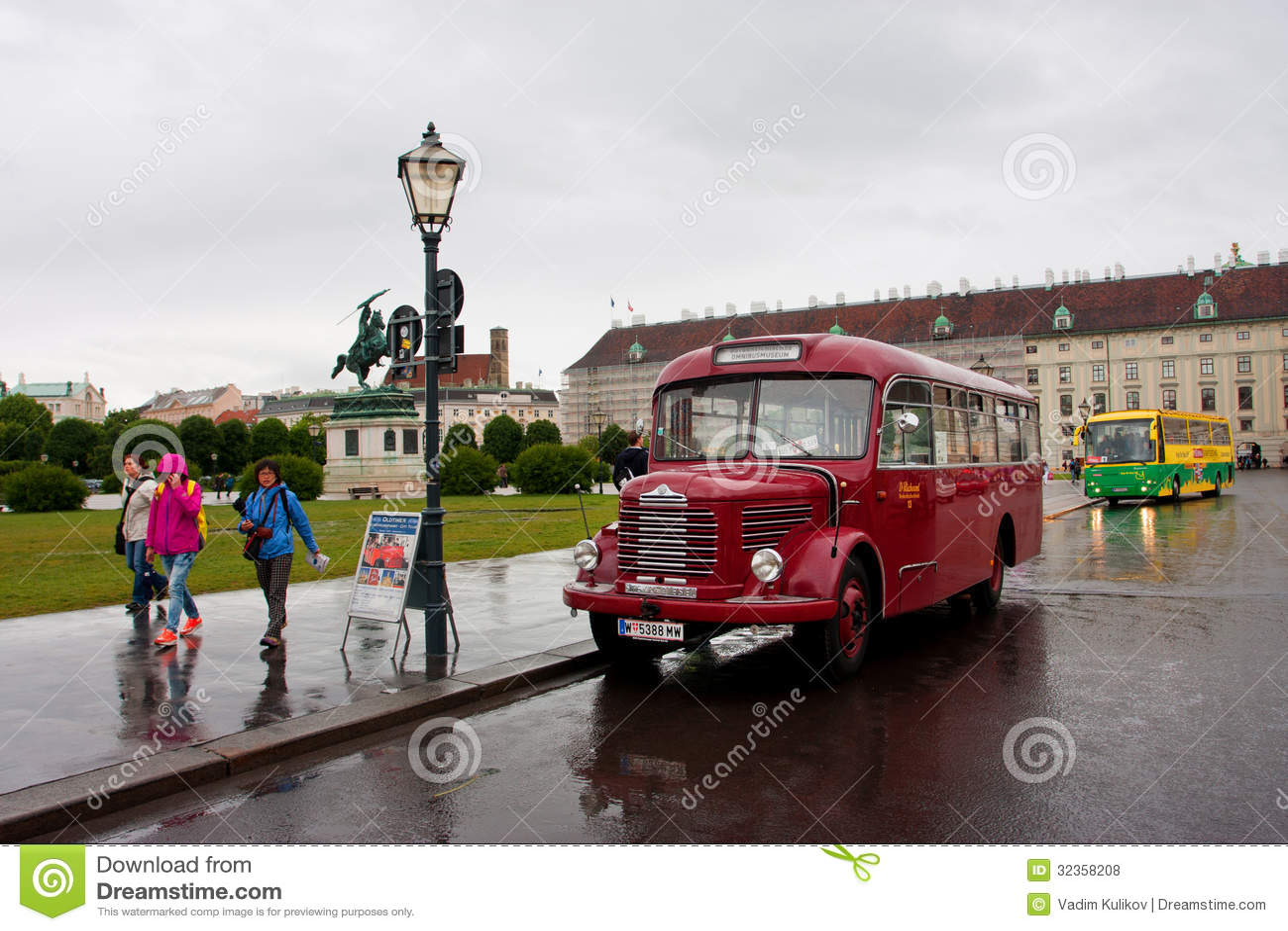 People Walk On Rainy Street Past The Antique Touristic Bus