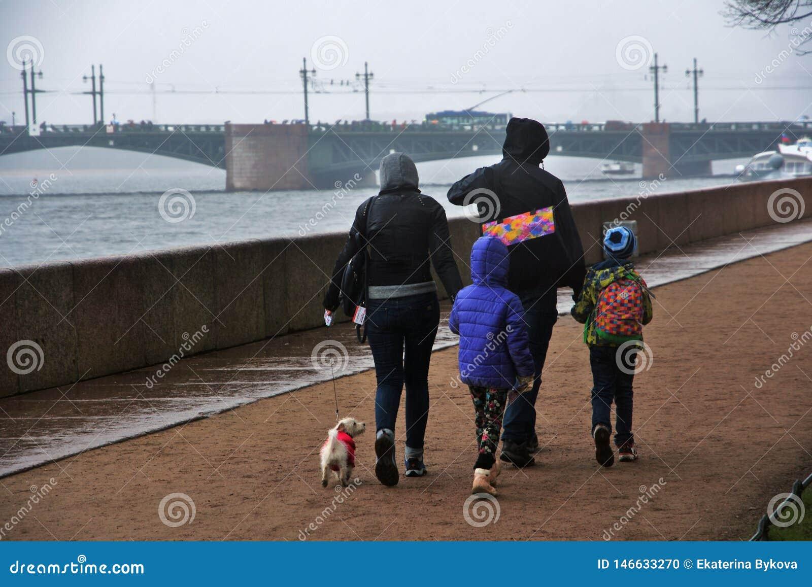People walk in Saint Petersburg under umbrella