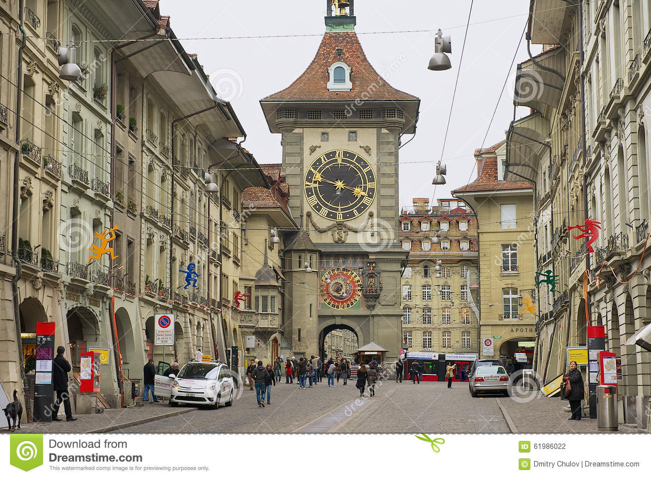 People Walk By The Street With The Historic Bern Clock