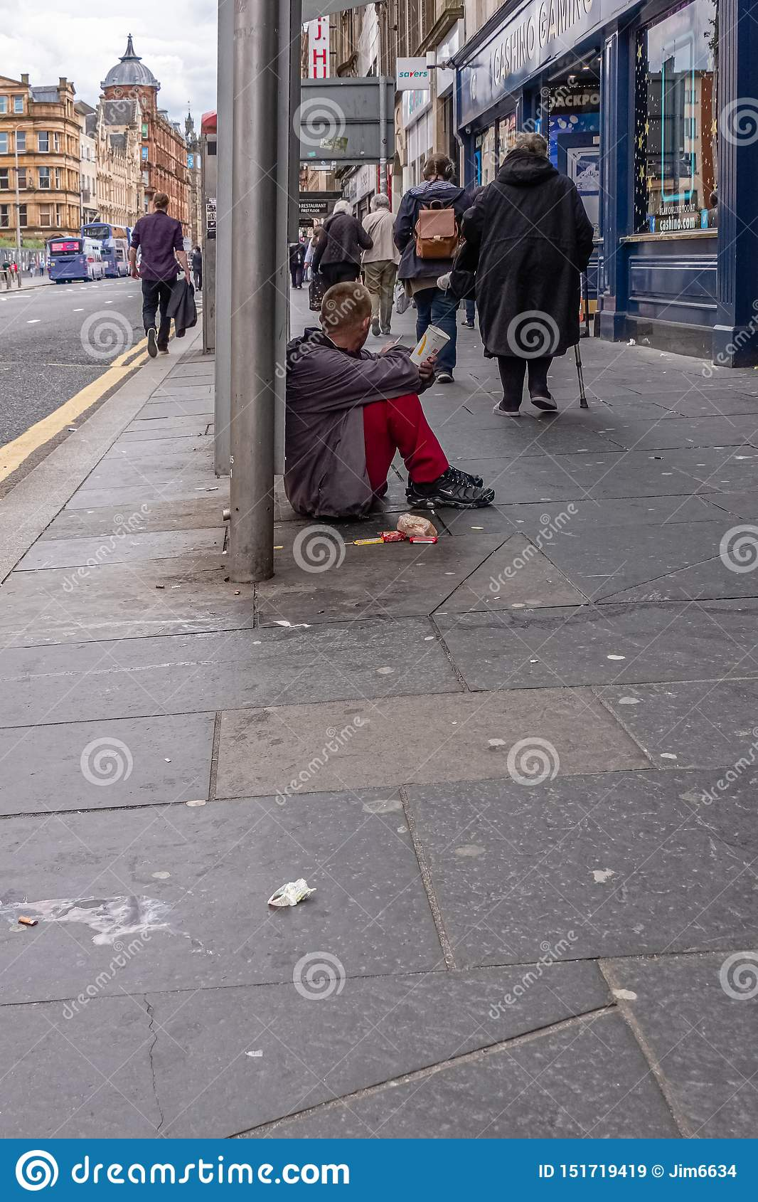 People walking past a male gentleman siting on the Dirty pavement with a McDonald`s paper cup appealing for money in Glasgow Cit
