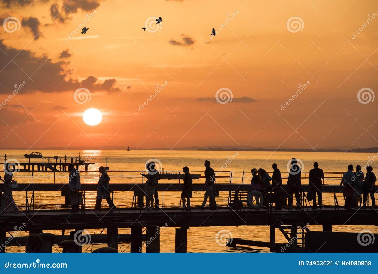 People walking on sunset over bridge on lake
