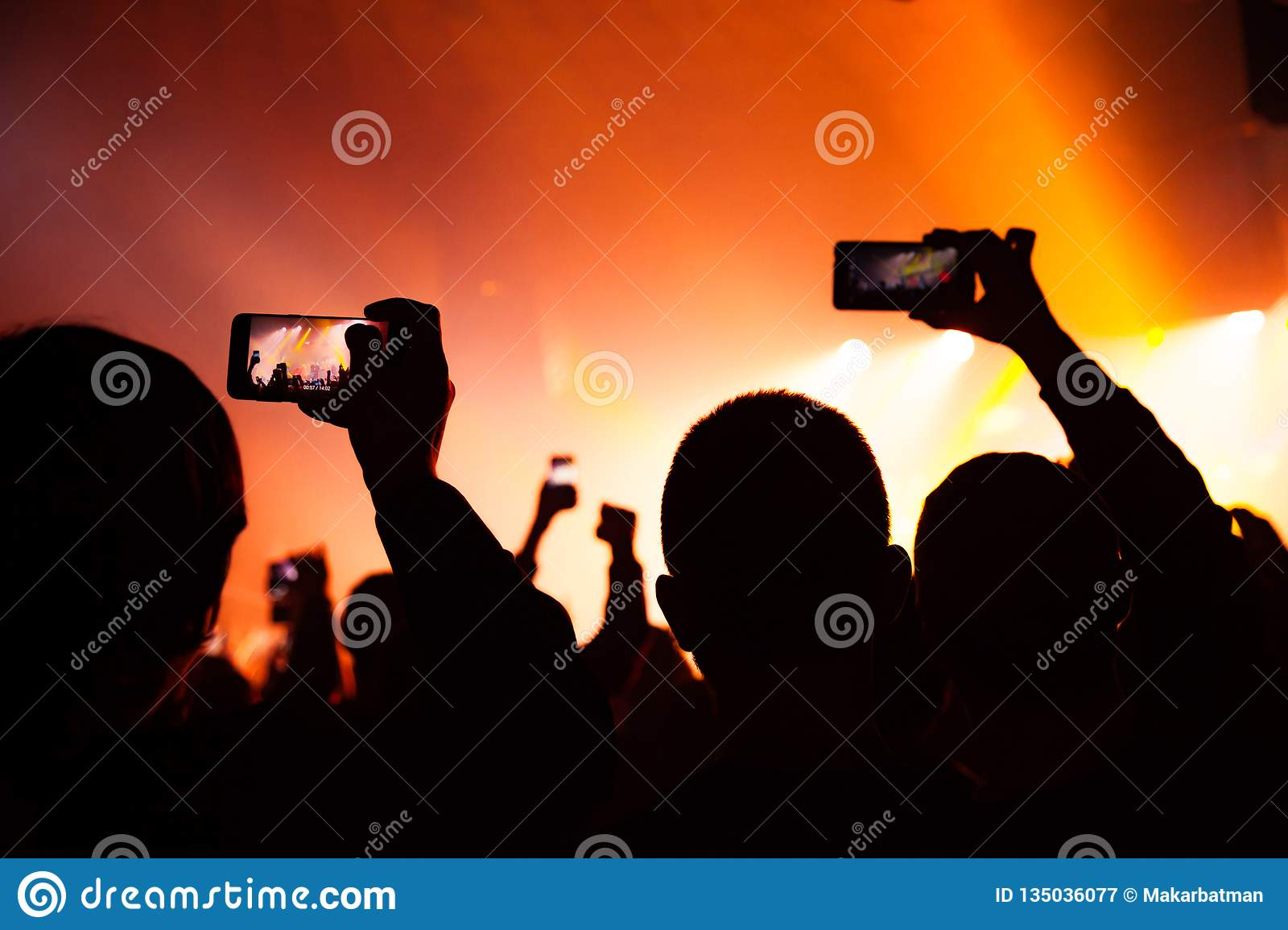 People watching a concert and someone shooting photo and video with a cellphone