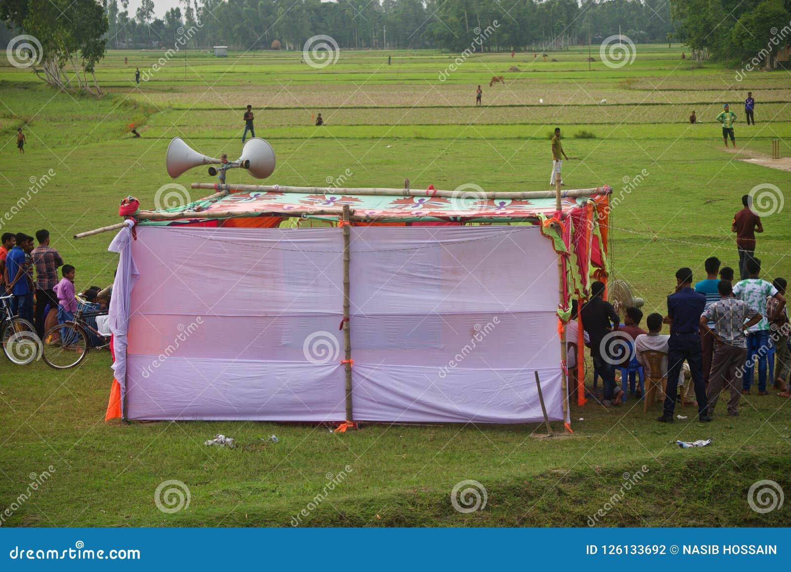People watching cricket games around a village ground