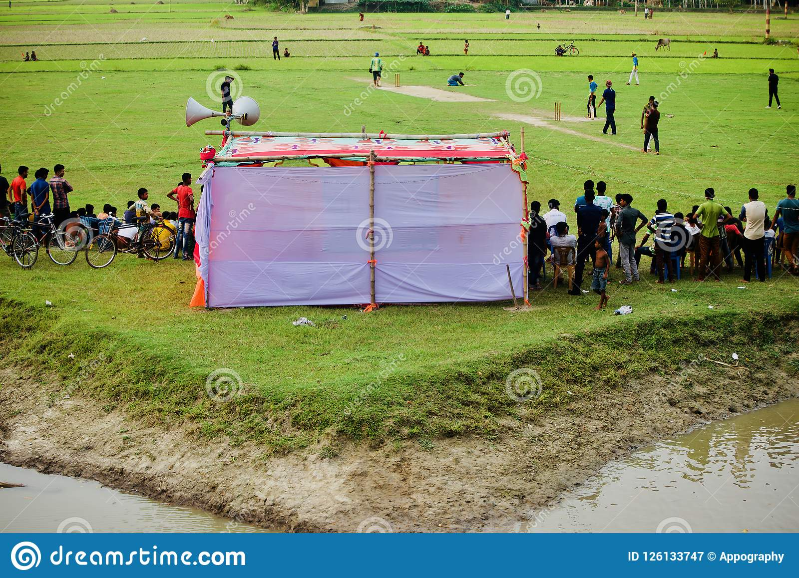 People watching cricket games around a village ground