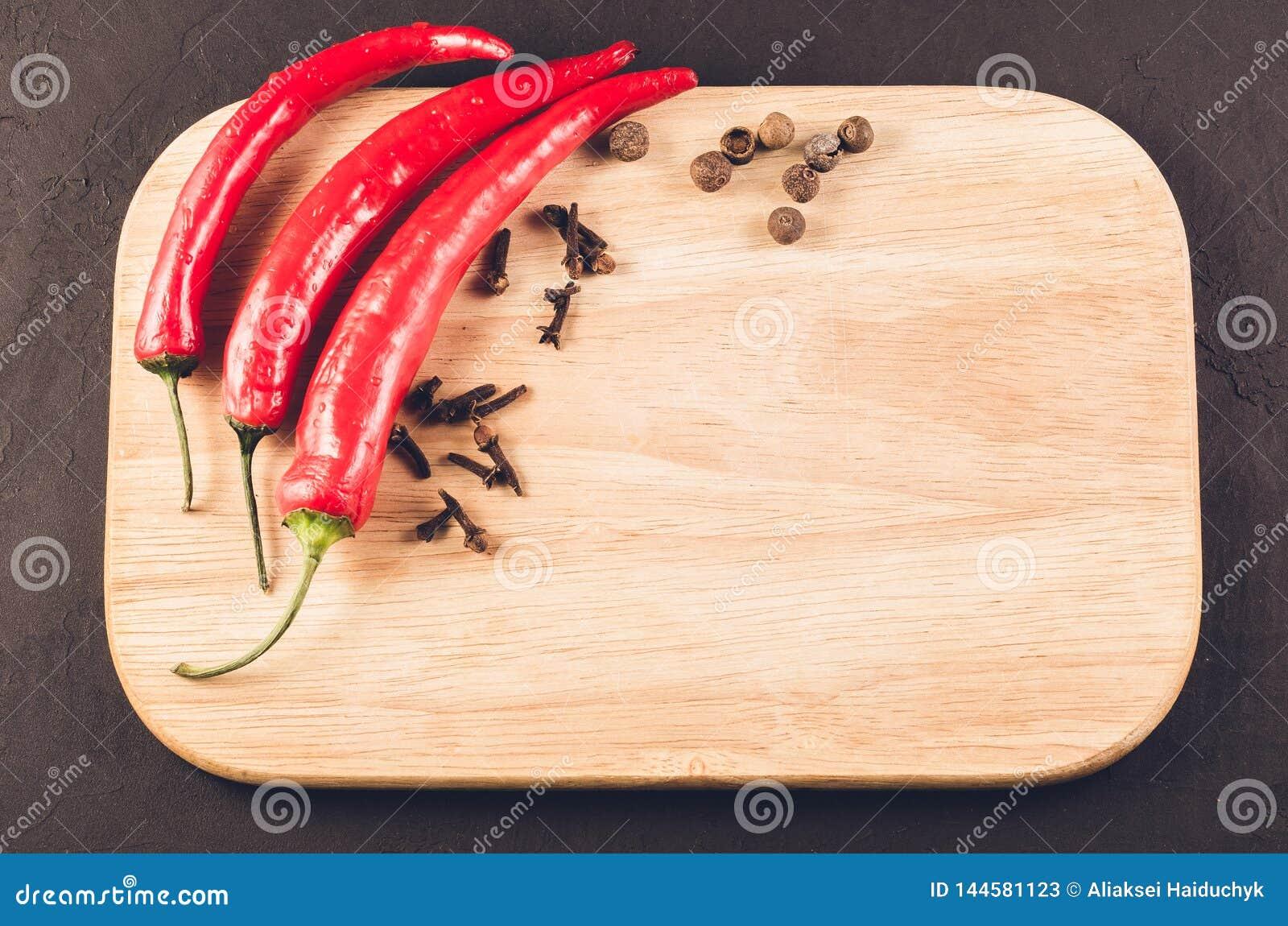 Peperoncini e spezie su un tagliere vuoto/peperoncini roventi e spezie roventi su un tagliere vuoto su un buio
