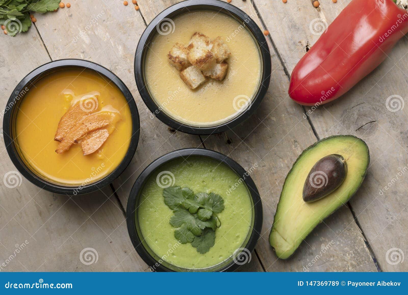 Peperone, mezzo avacado e cucchiaio vicino alle minestre del vegano in contenitori di alimento, pasto pronto da mangiare