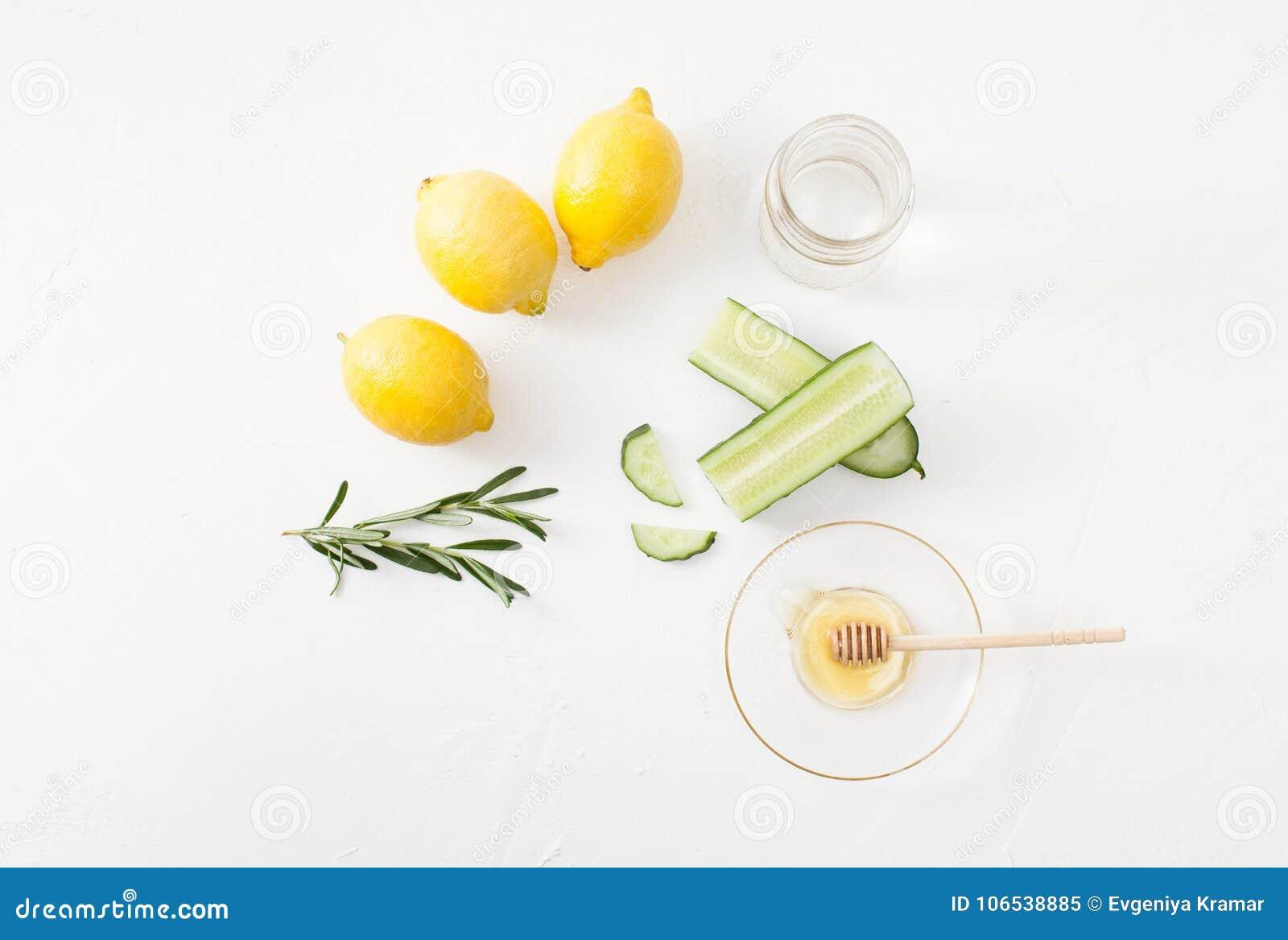 Pepino, mel e alecrins e limões cortados no fundo branco