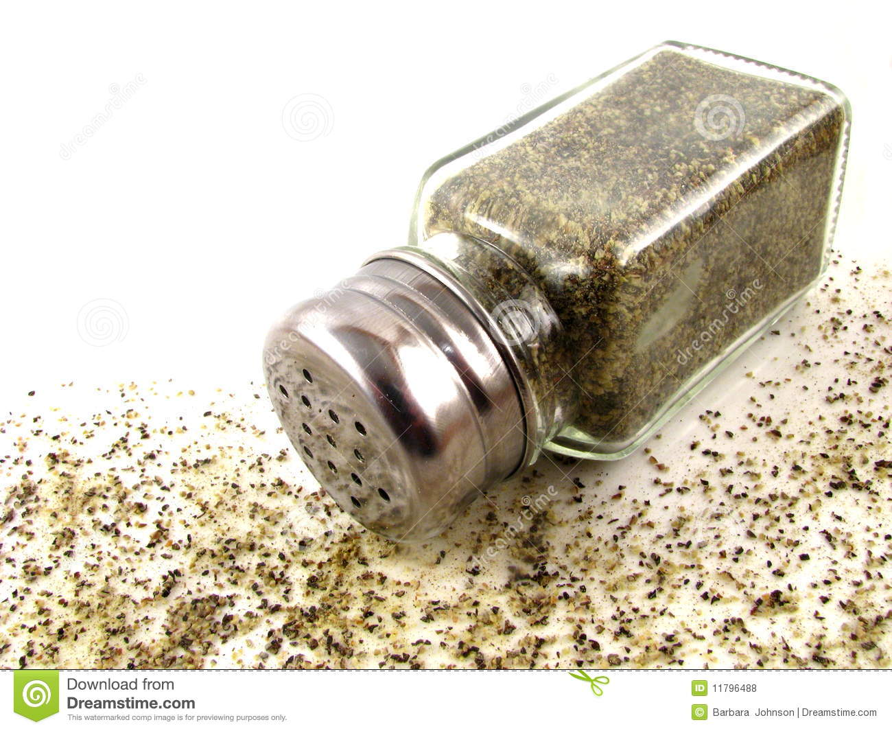 Glass pepper shaker with spilled ground black pepper on a white ...