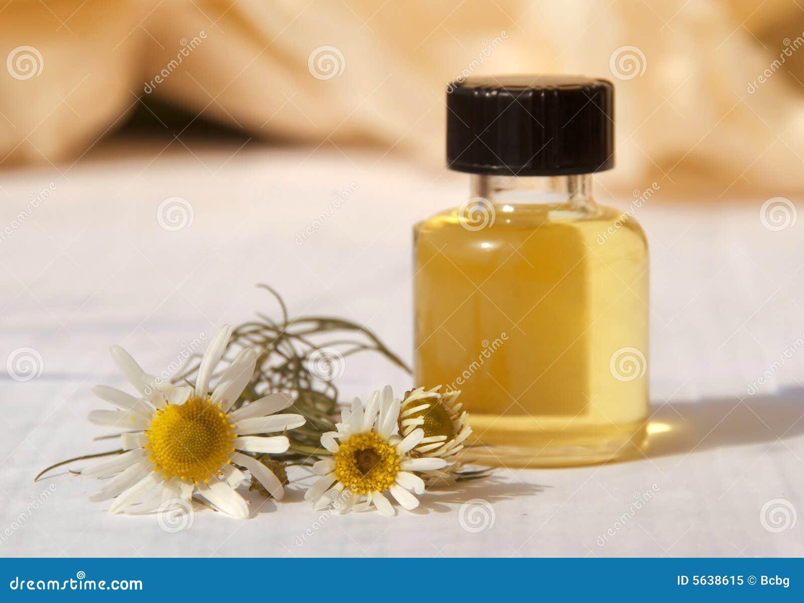 Pequeña botella con petróleo esencial y la flor del camo