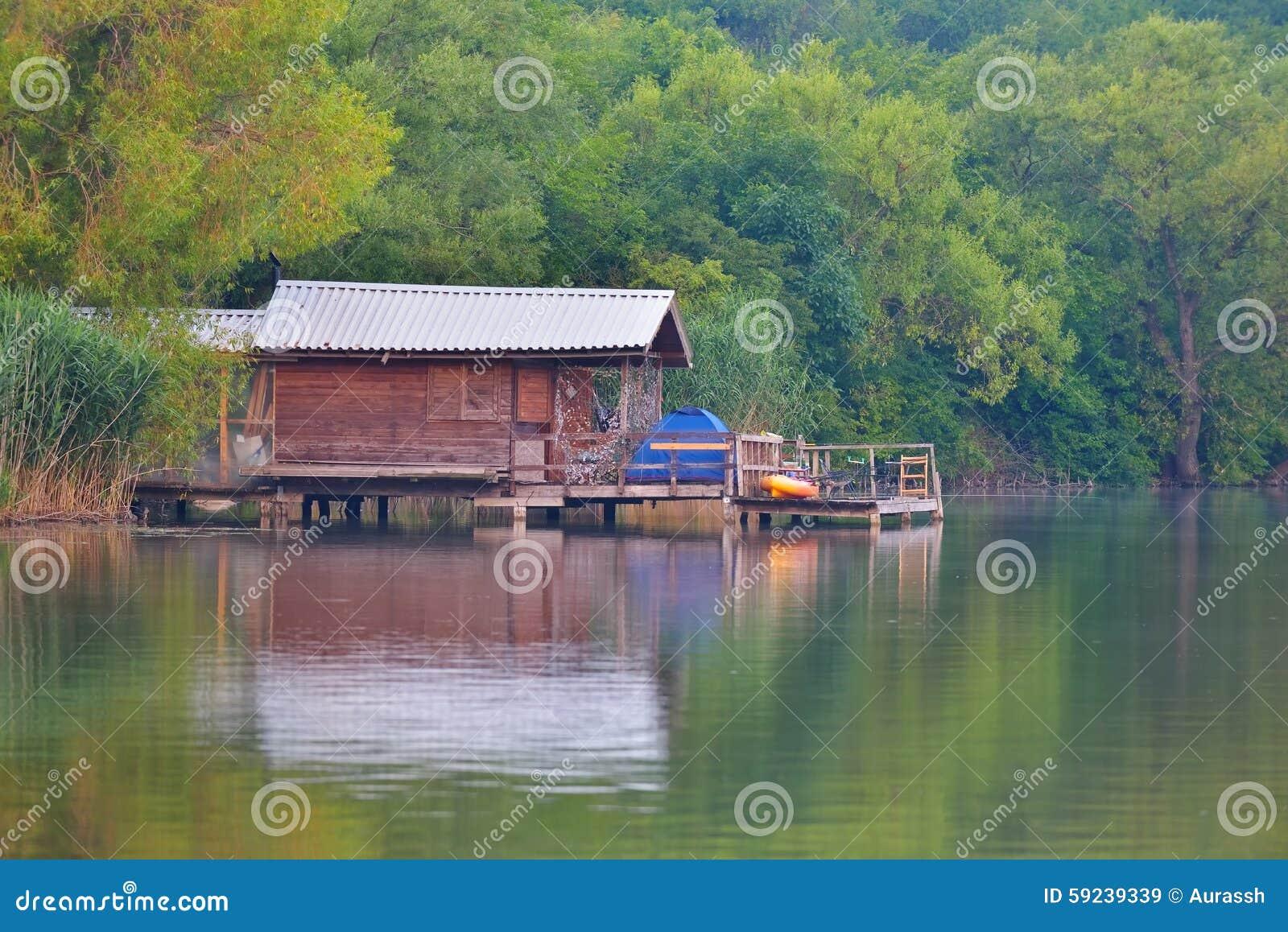 Pequeña cabaña de los días de fiesta reflejada en el lago