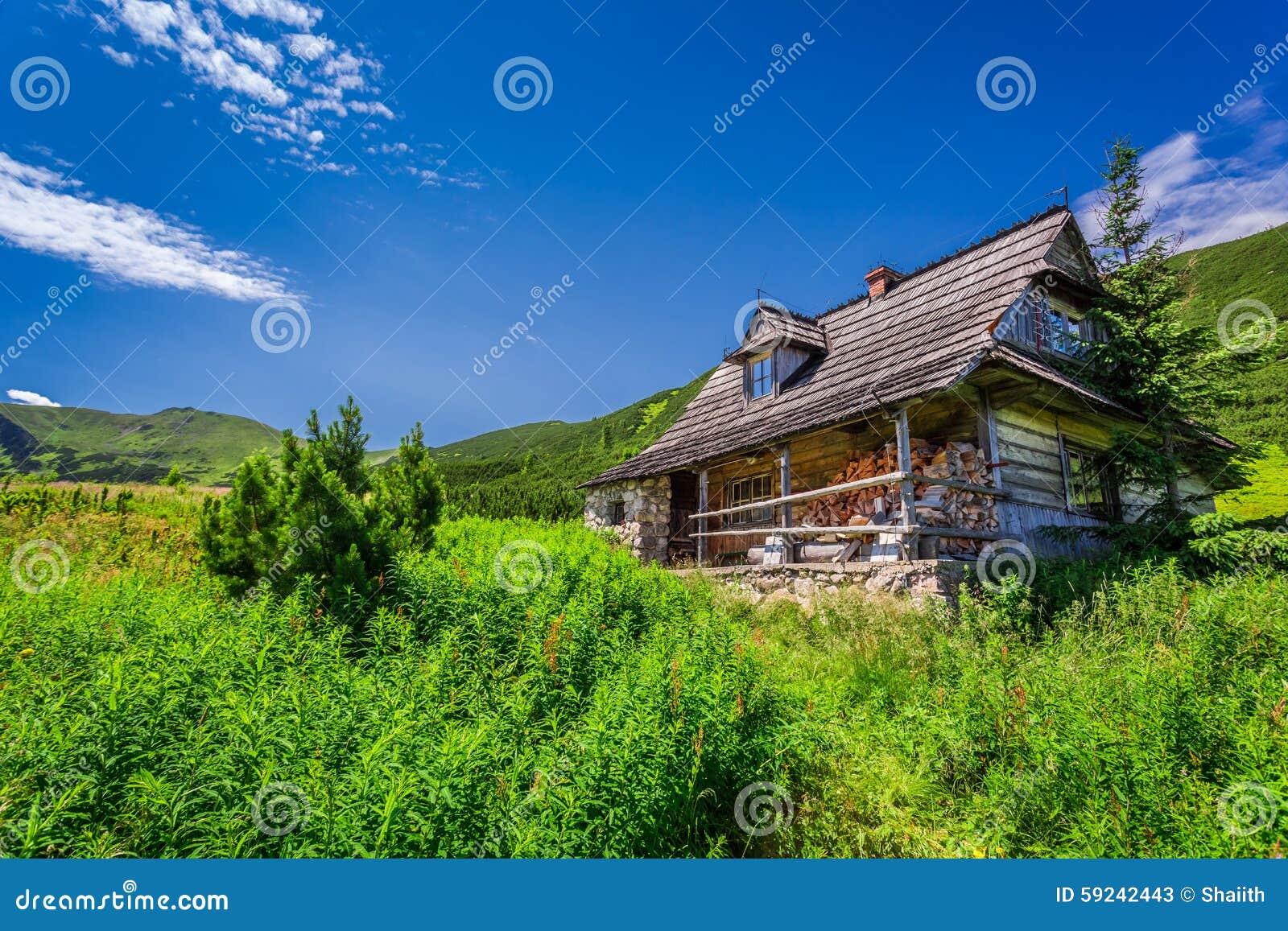 Pequeña cabaña en un valle de la montaña en la salida del sol