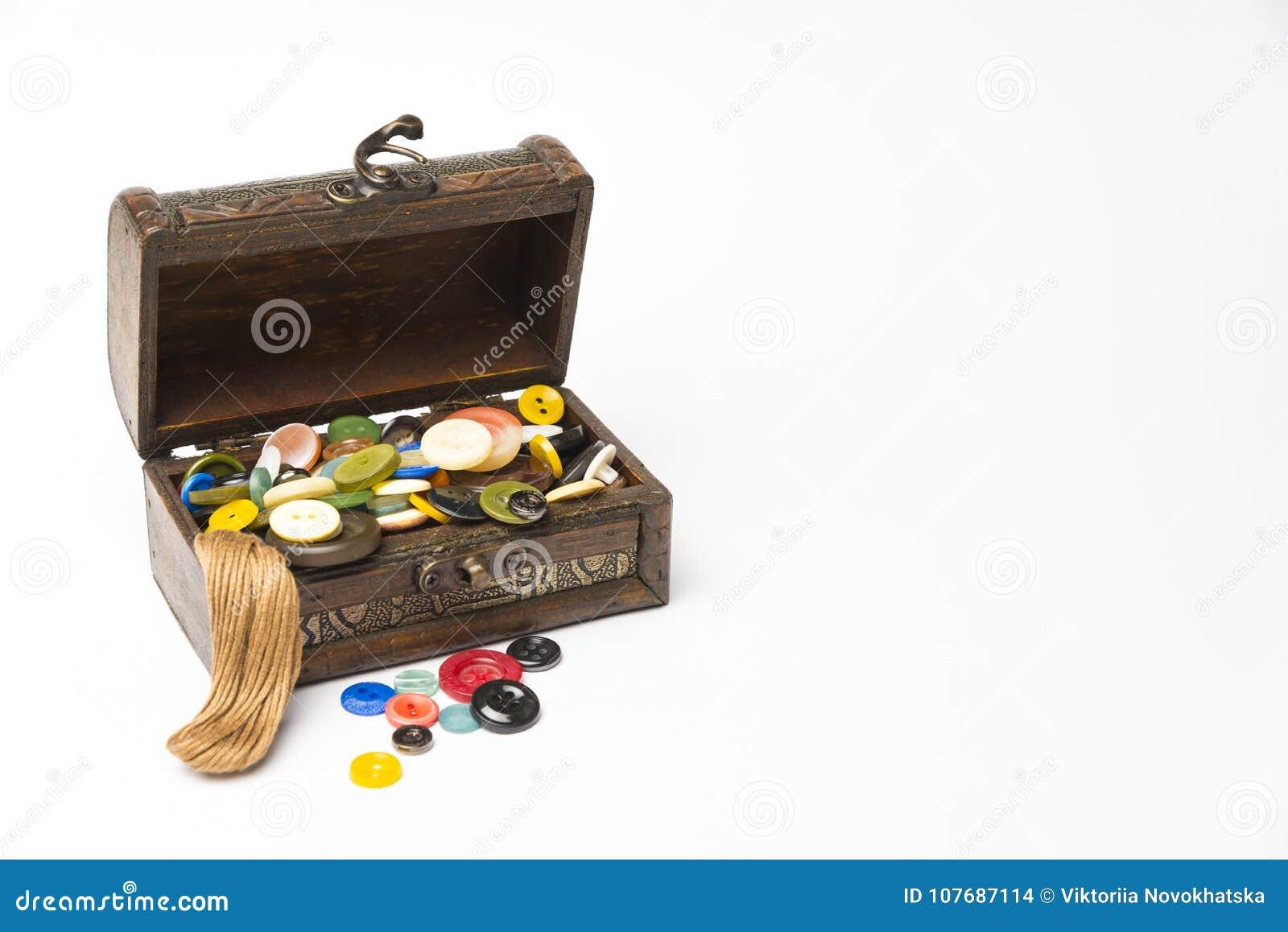 Pequeña caja de madera con los botones y los hilos