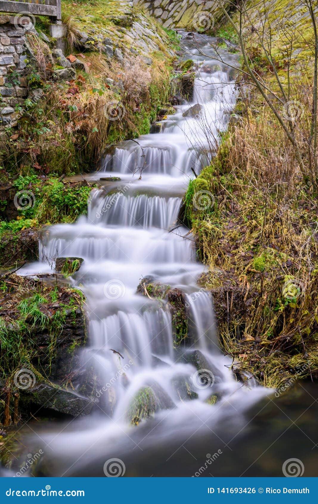 Pequeña cascada en Sajonia en una colina verde
