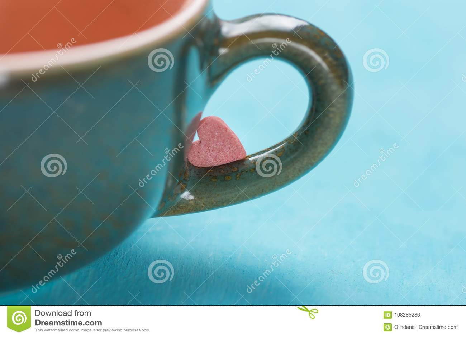 Pequeña forma rosada Sugar Candy del corazón en la manija de la taza de té del café en fondo azul claro valentines