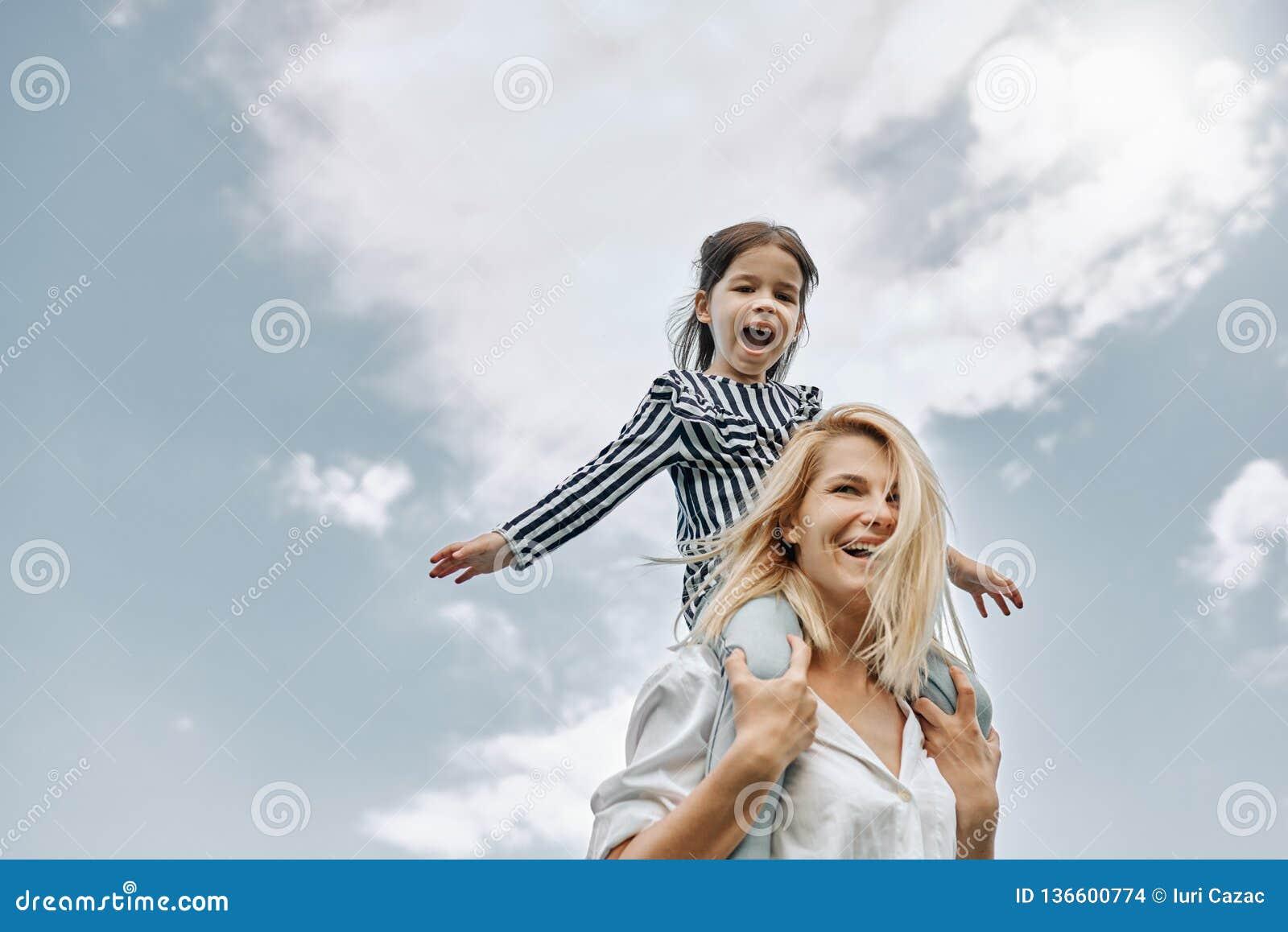 Pequeña hija divertida feliz en un paseo del transporte por ferrocarril con su madre feliz en el fondo del cielo Mujer de amor y