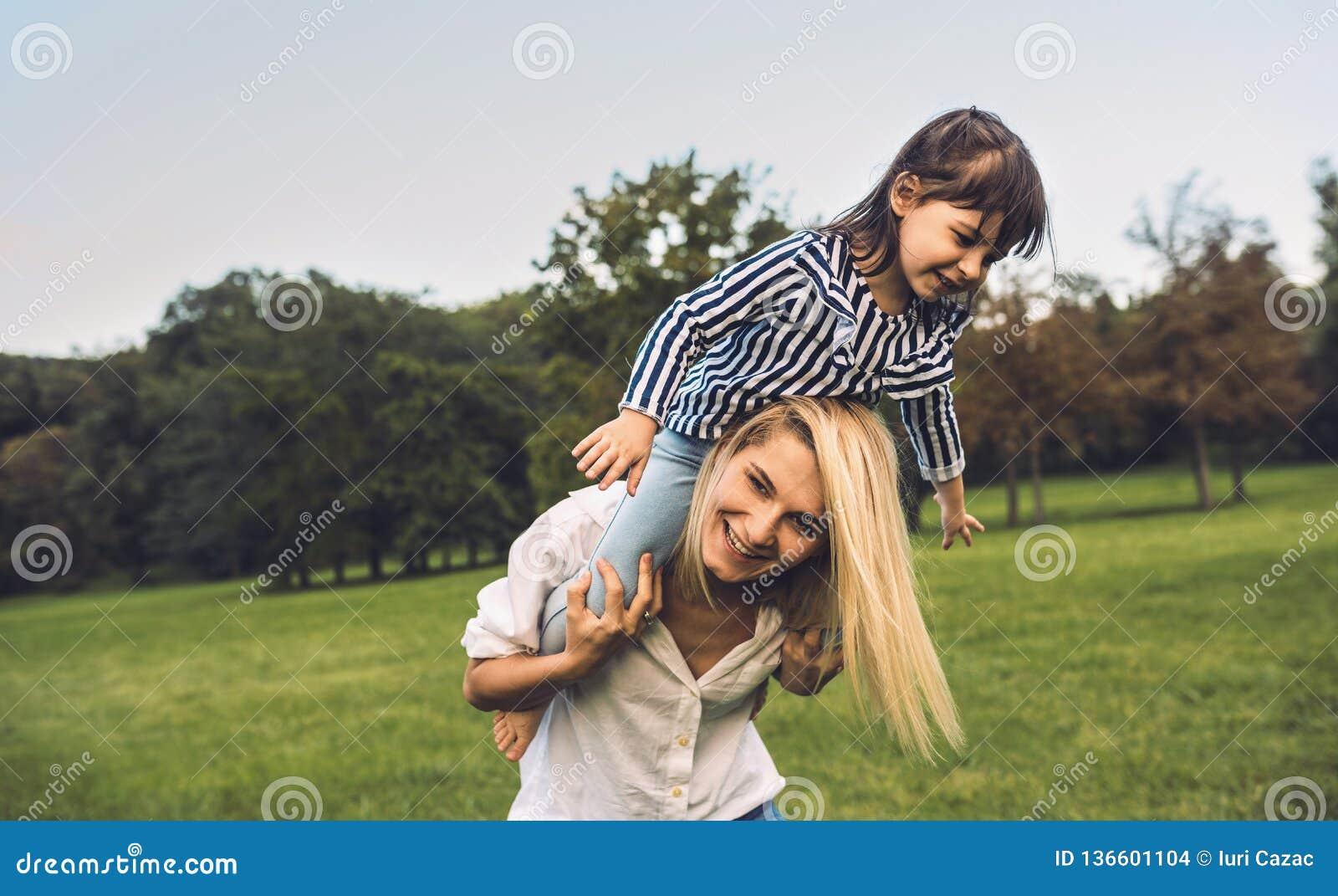 Pequeña hija divertida linda en un paseo del transporte por ferrocarril con su madre sonriente Mujer de amor y su niña que juegan