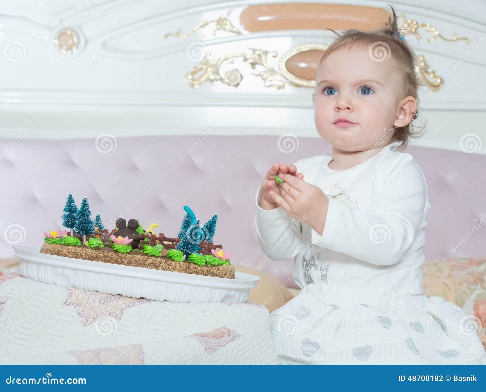 Pequeña muchacha caucásica del niño en feliz cumpleaños con la torta en casa