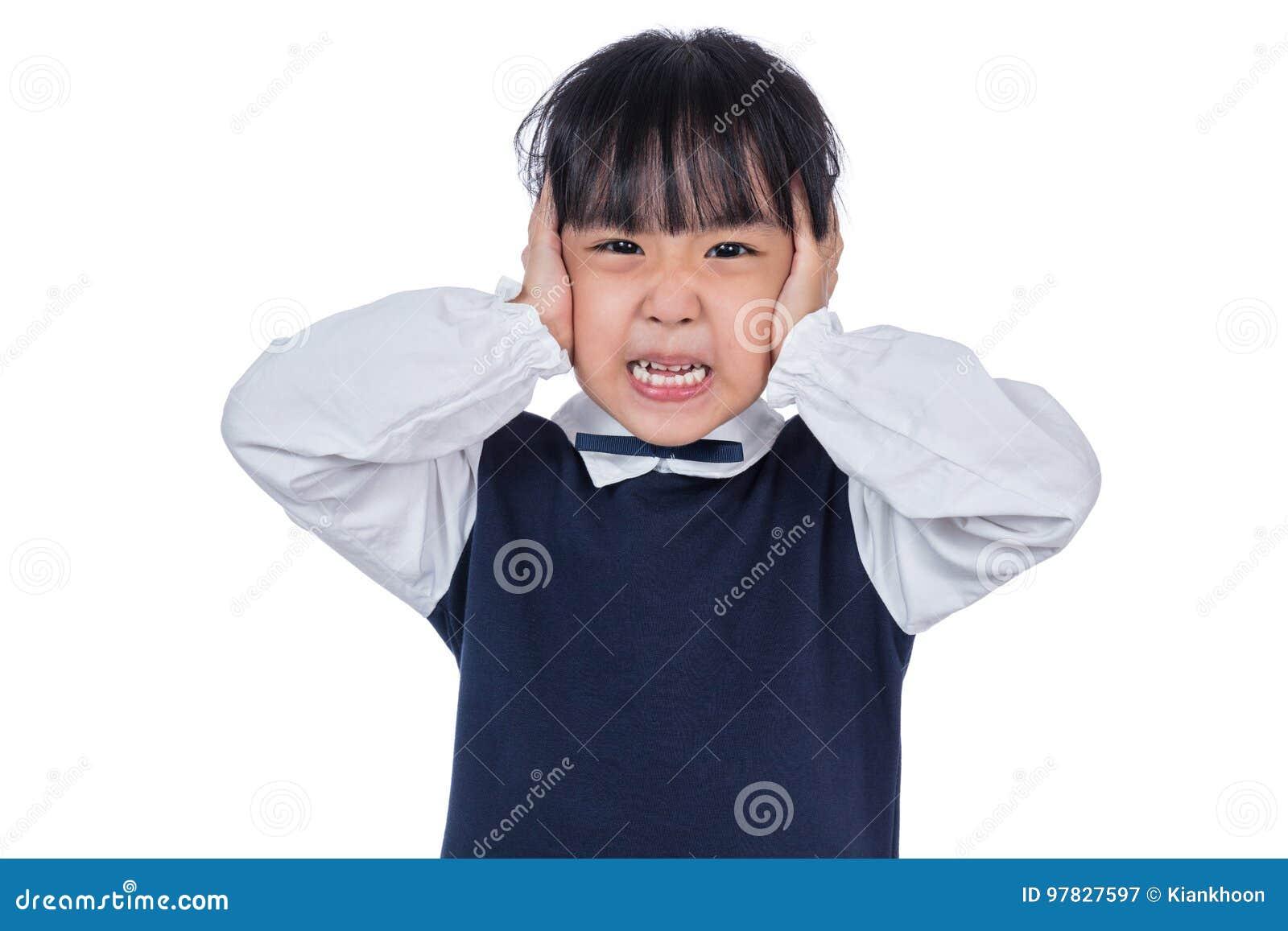 Pequeña muchacha china asiática que cubre sus oídos con las manos