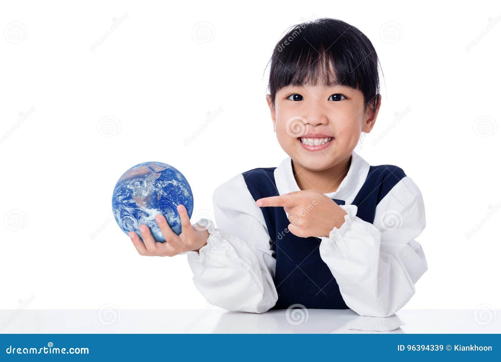 Pequeña muchacha china asiática que sostiene un globo del mundo
