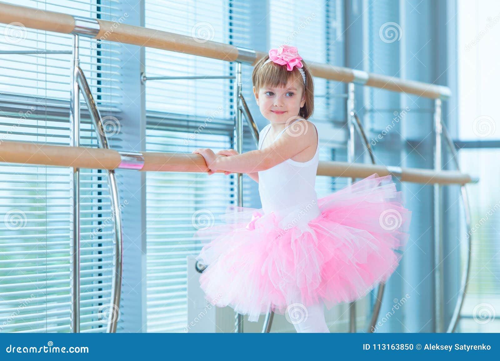 427dd3651ed Pequeña muchacha de la bailarina en un tutú rosado Niño adorable que baila  ballet clásico en