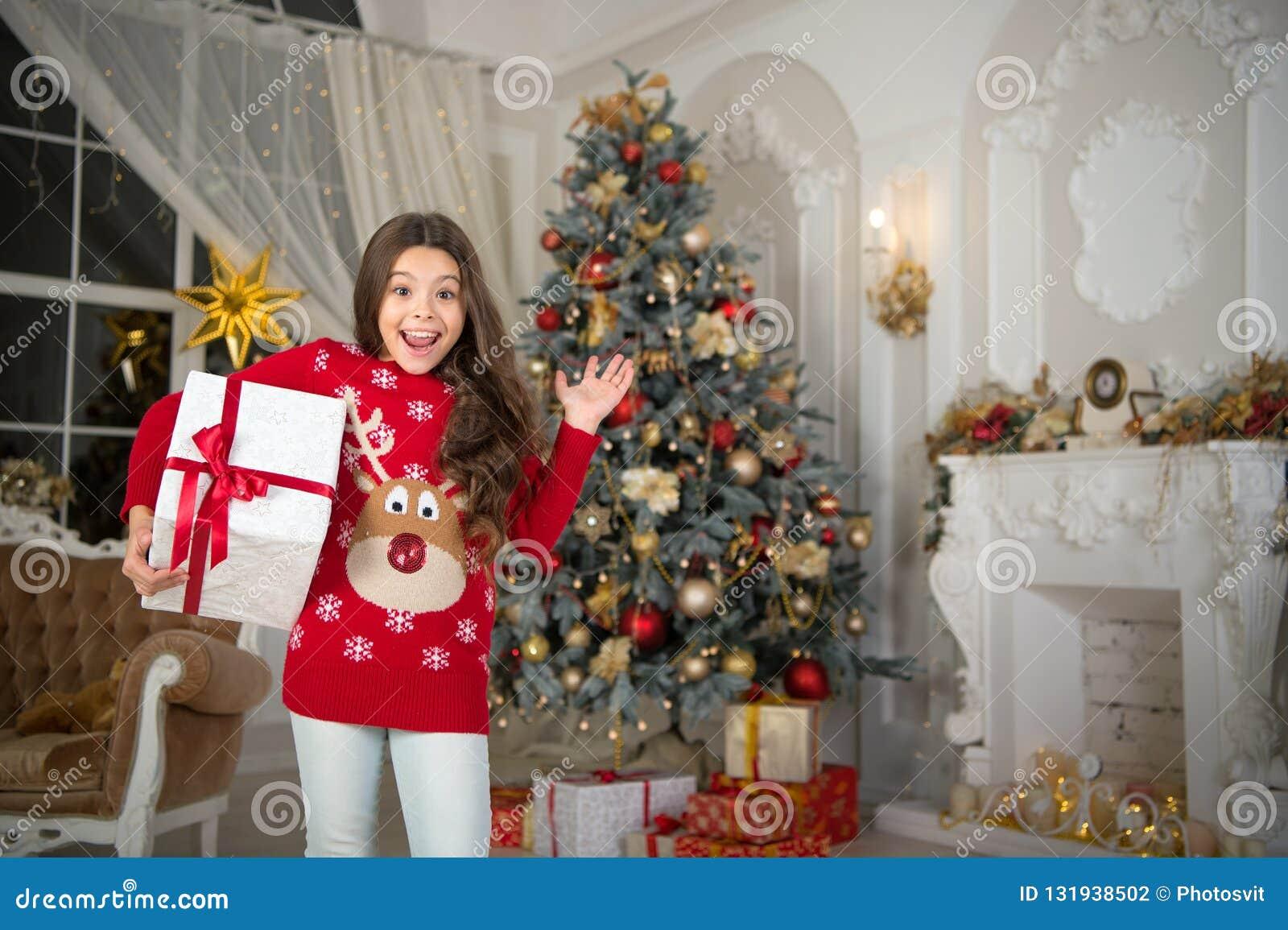 Pequeña muchacha feliz en la Navidad Feliz Año Nuevo La mañana antes de Navidad Día de fiesta del Año Nuevo Navidad El niño goza