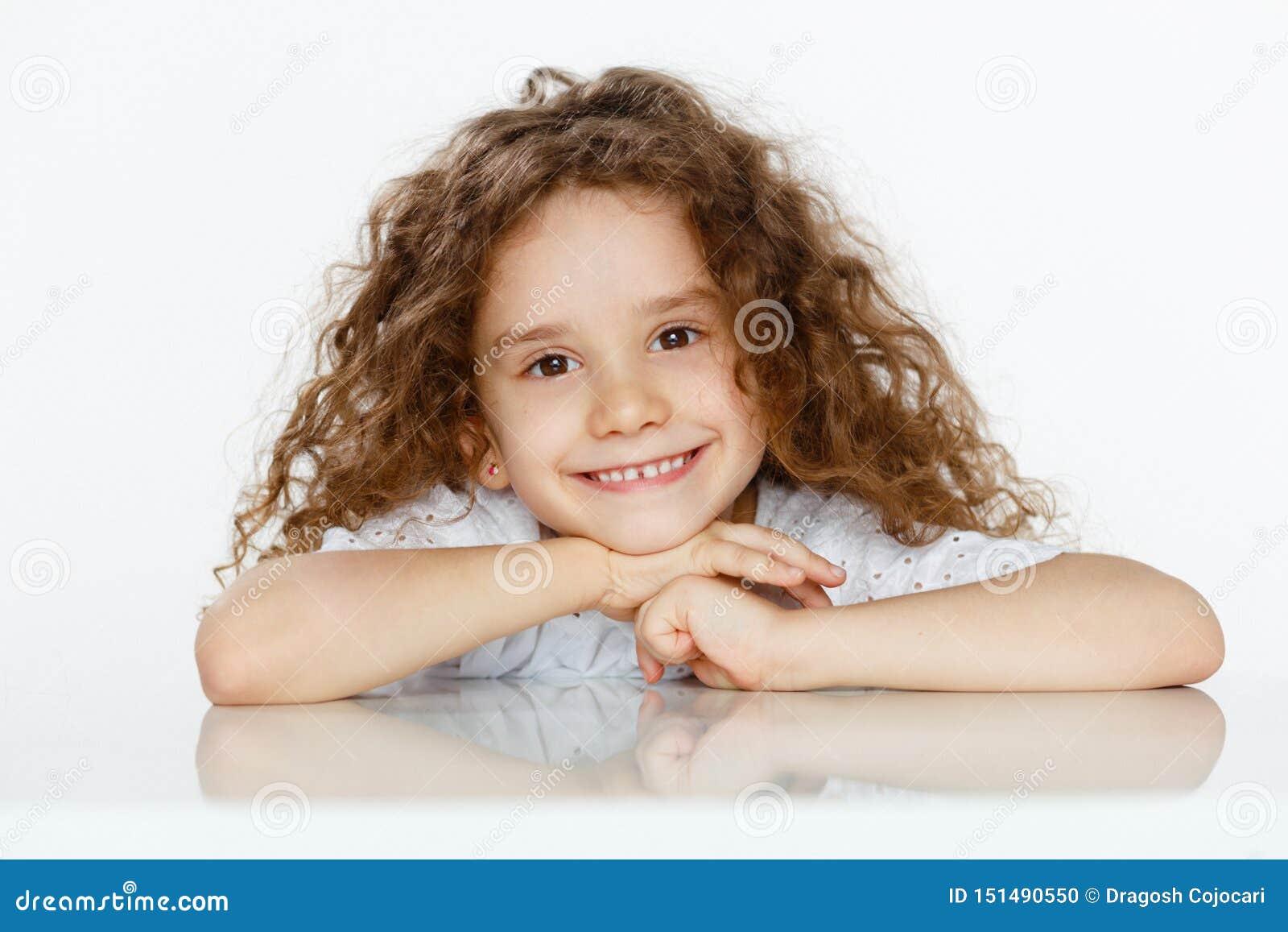 Pequeña muchacha linda adorable con el pelo rizado en la blusa blanca, asentada en una tabla, mirando la cámara, sobre el fondo b
