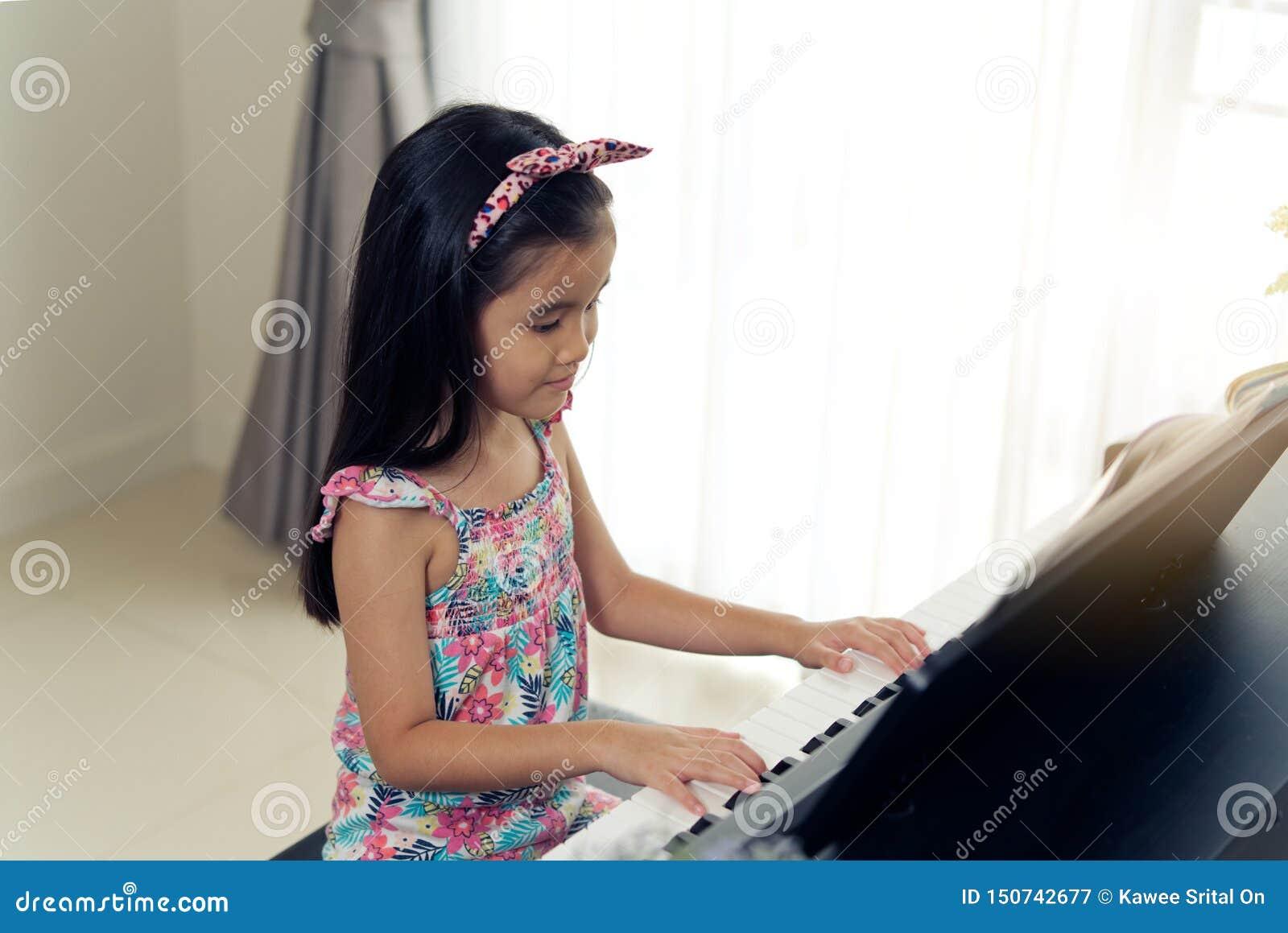 Pequeña muchacha linda asiática joven que juega el piano electrónico en casa