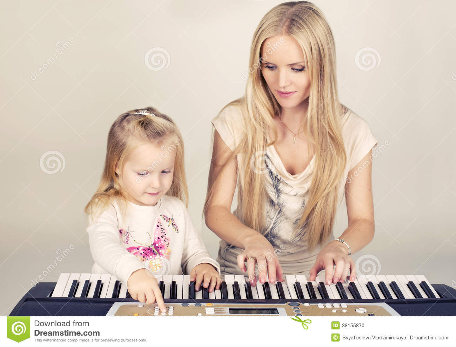 Pequeña muchacha linda con su mamá que juega en el sintetizador