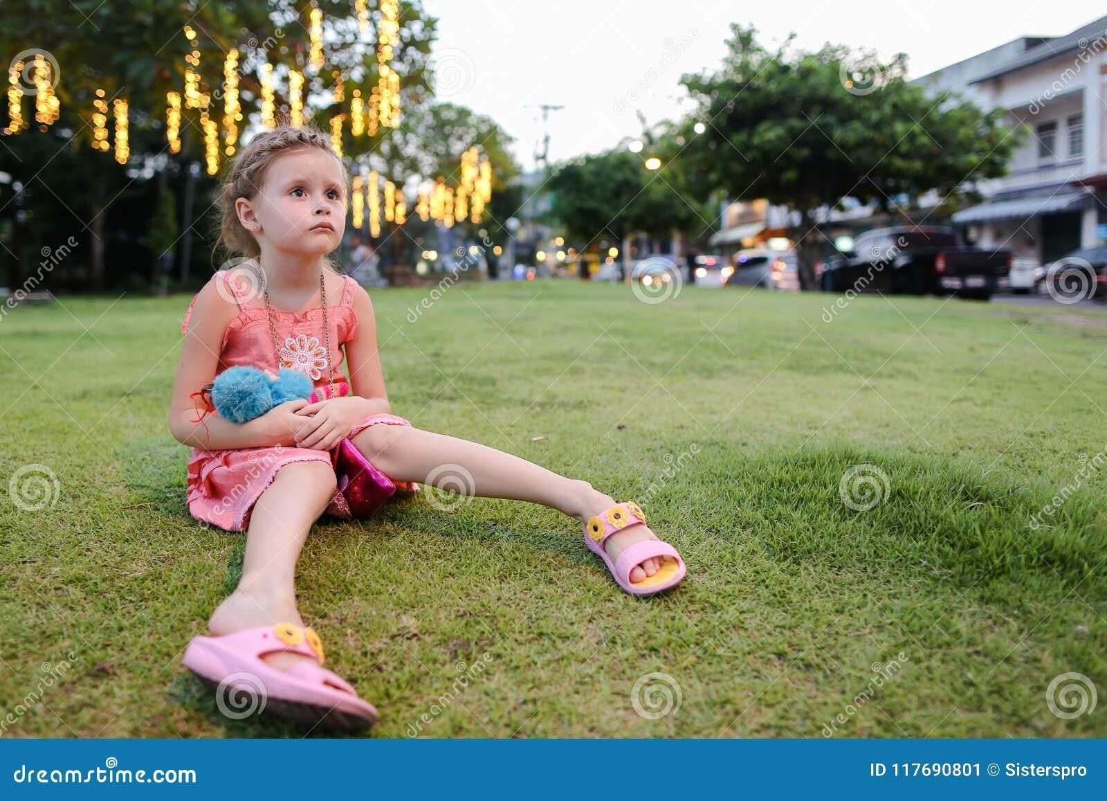 Pequeña muchacha linda que se sienta en el césped de la hierba, empleando fondo